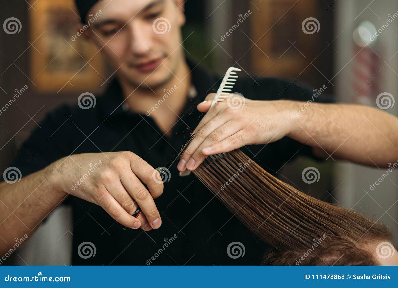 De handen van jonge kapper die tot kapsel maken aan de aantrekkelijke gebaarde mens in herenkapper