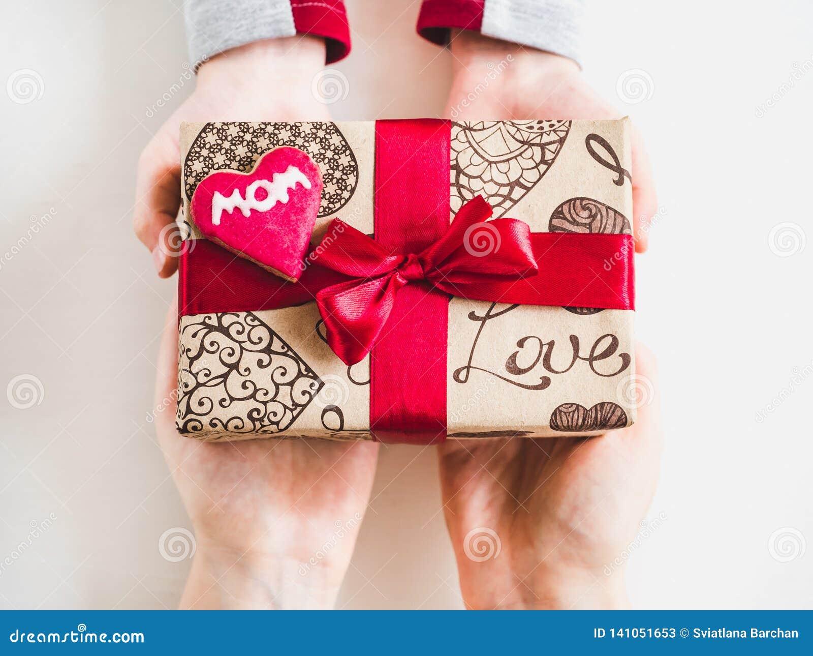 De handen van kinderen en een doos met een gift