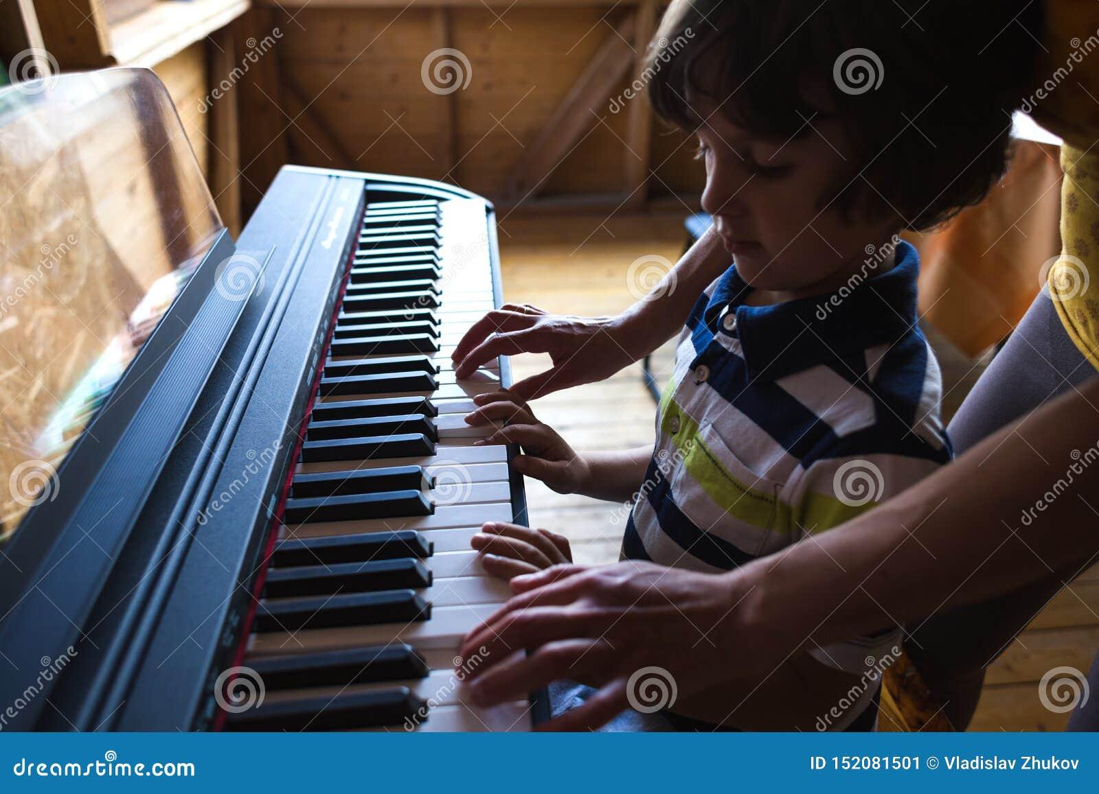 De handen van kinderen en van vrouwen op de pianosleutels
