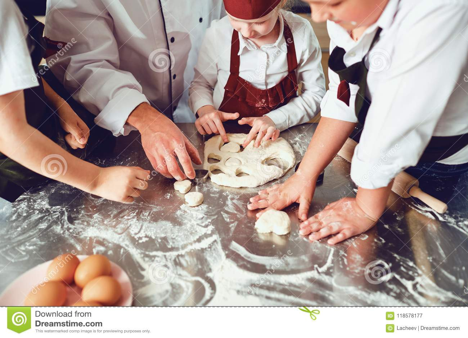 De handen van kinderenclose-up koken een koekje op de lijst