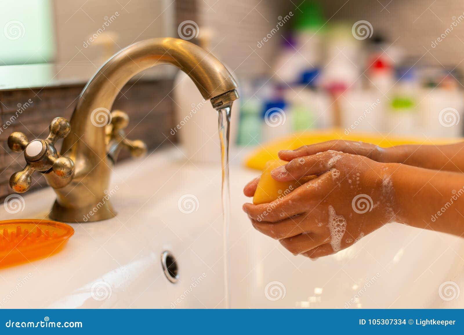 De handen van de kindwas bij de badkamerstapkraan