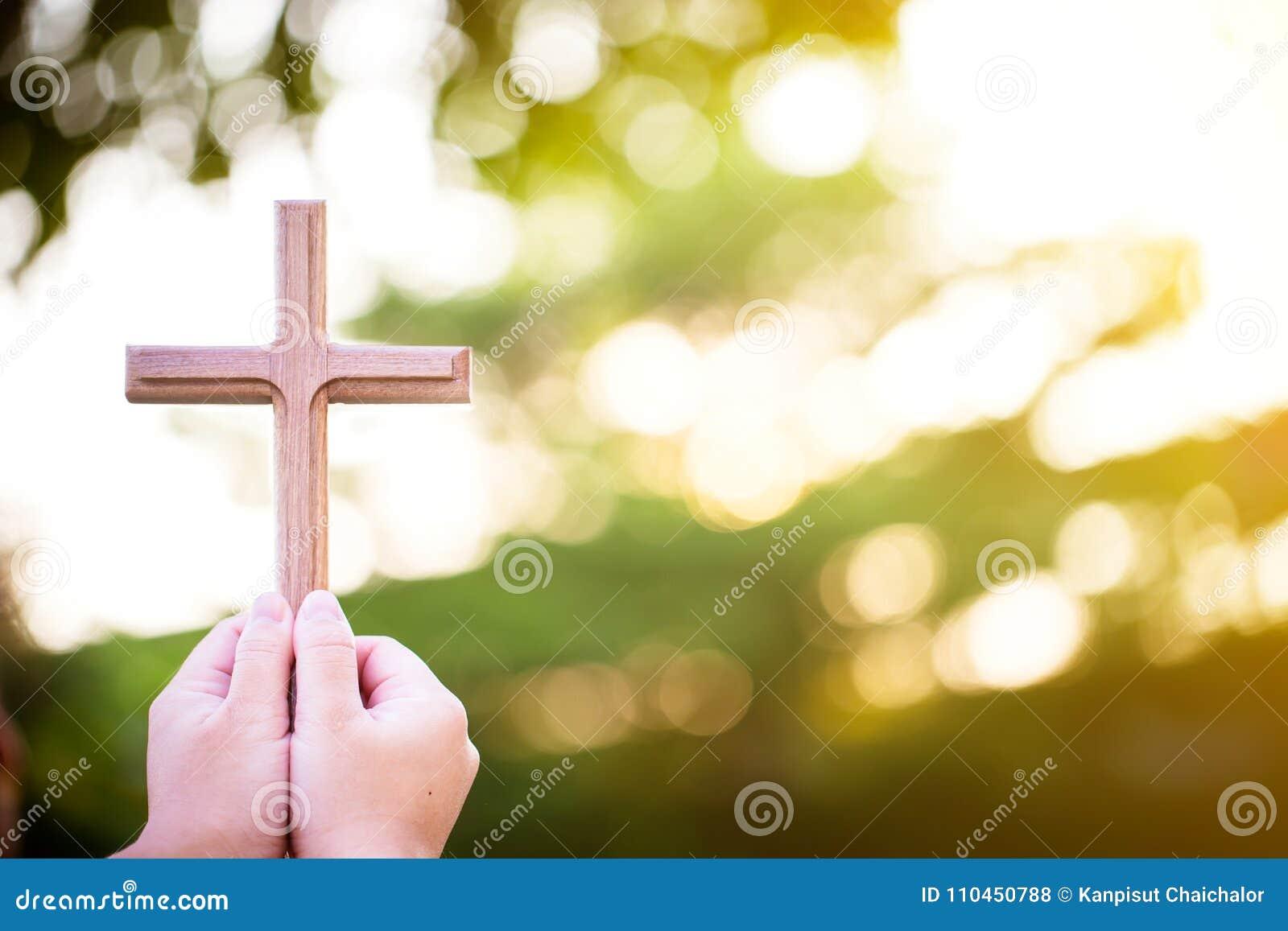 De handen van de persoonspalm om heilig kruis, kruisbeeld te houden om te aanbidden