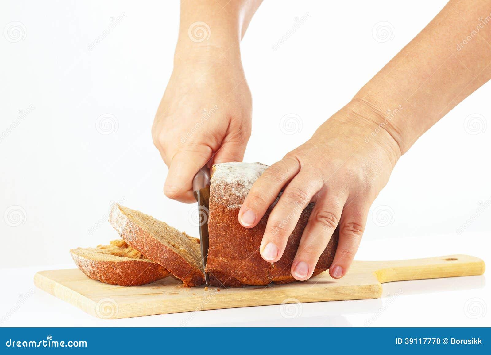 De handen van vrouwen met een mes gesneden roggebrood