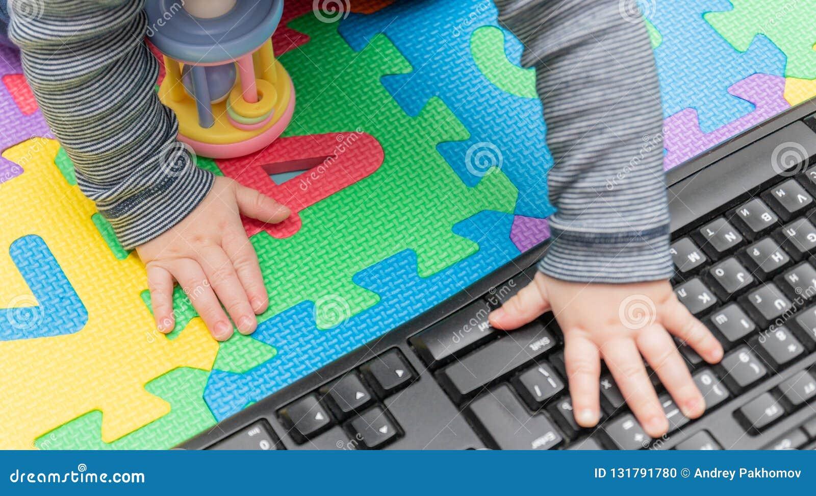 De handen van weinig baby, op een computermuis en een toetsenbord - kindontwikkeling, die vertrouwd met technologie sinds hun vro