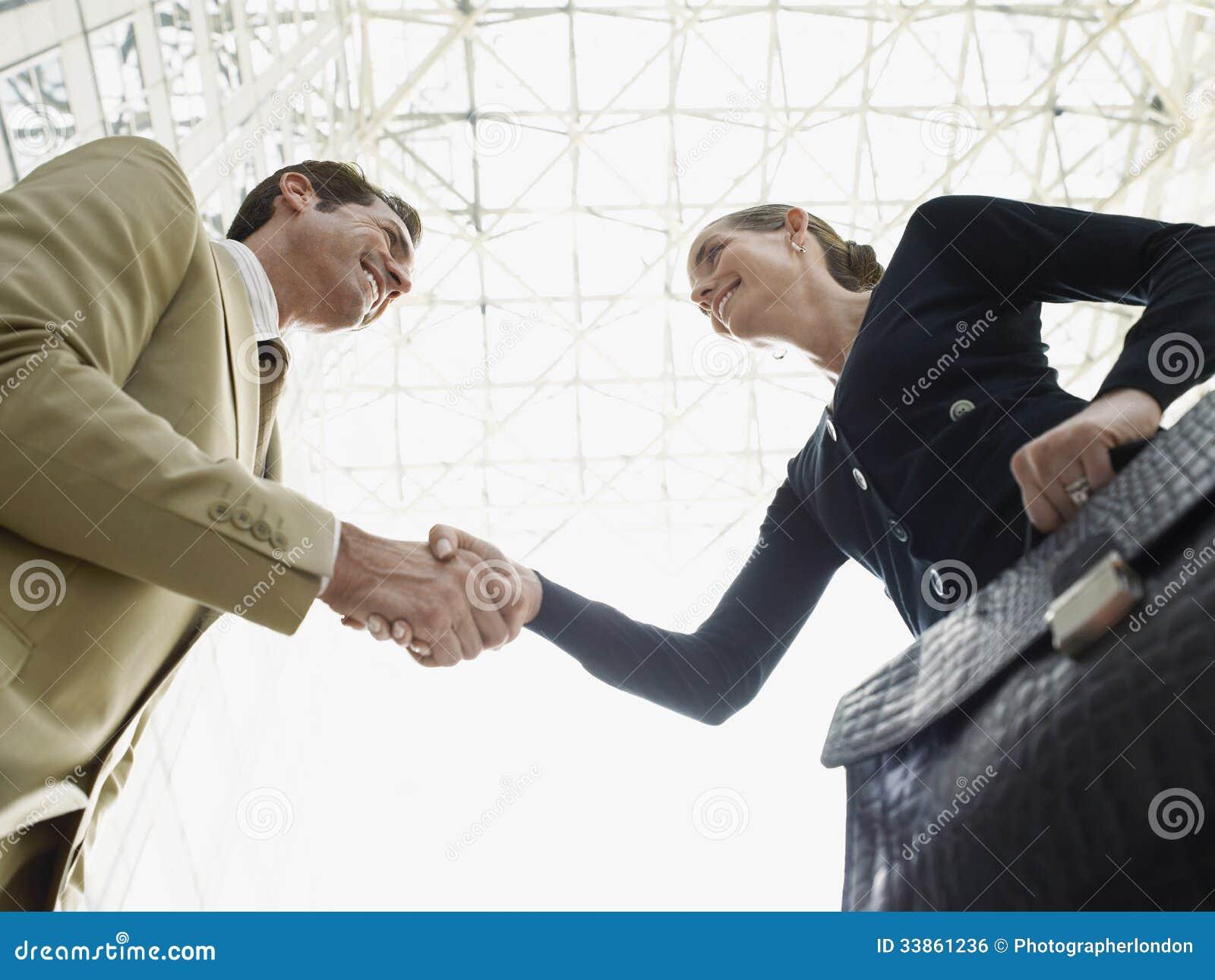 De Handen van zakenmanand businesswoman shaking tegen Plafond