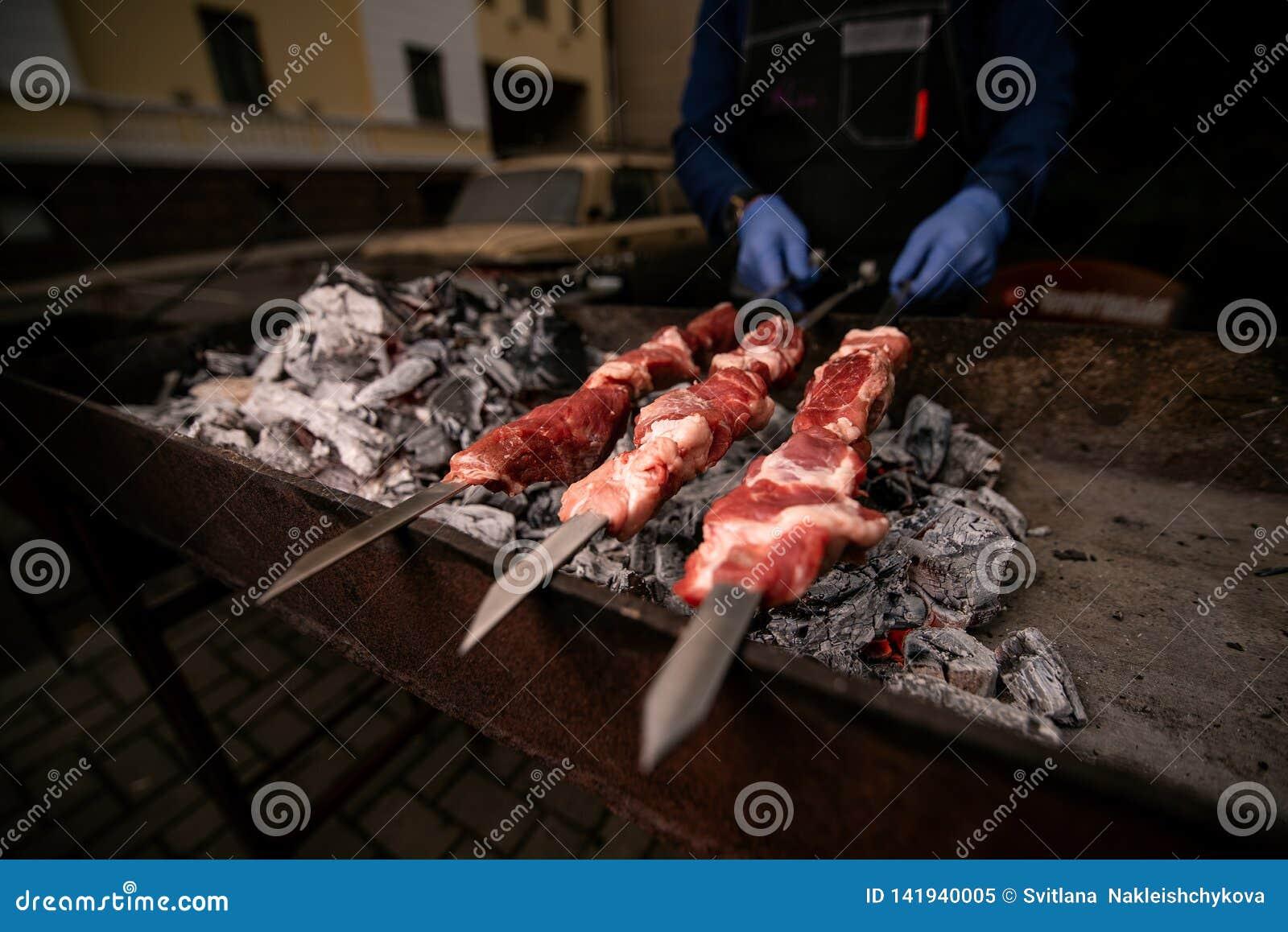 De handenkoks in blauwe handschoenen houden vleespennen met vlees op de grill