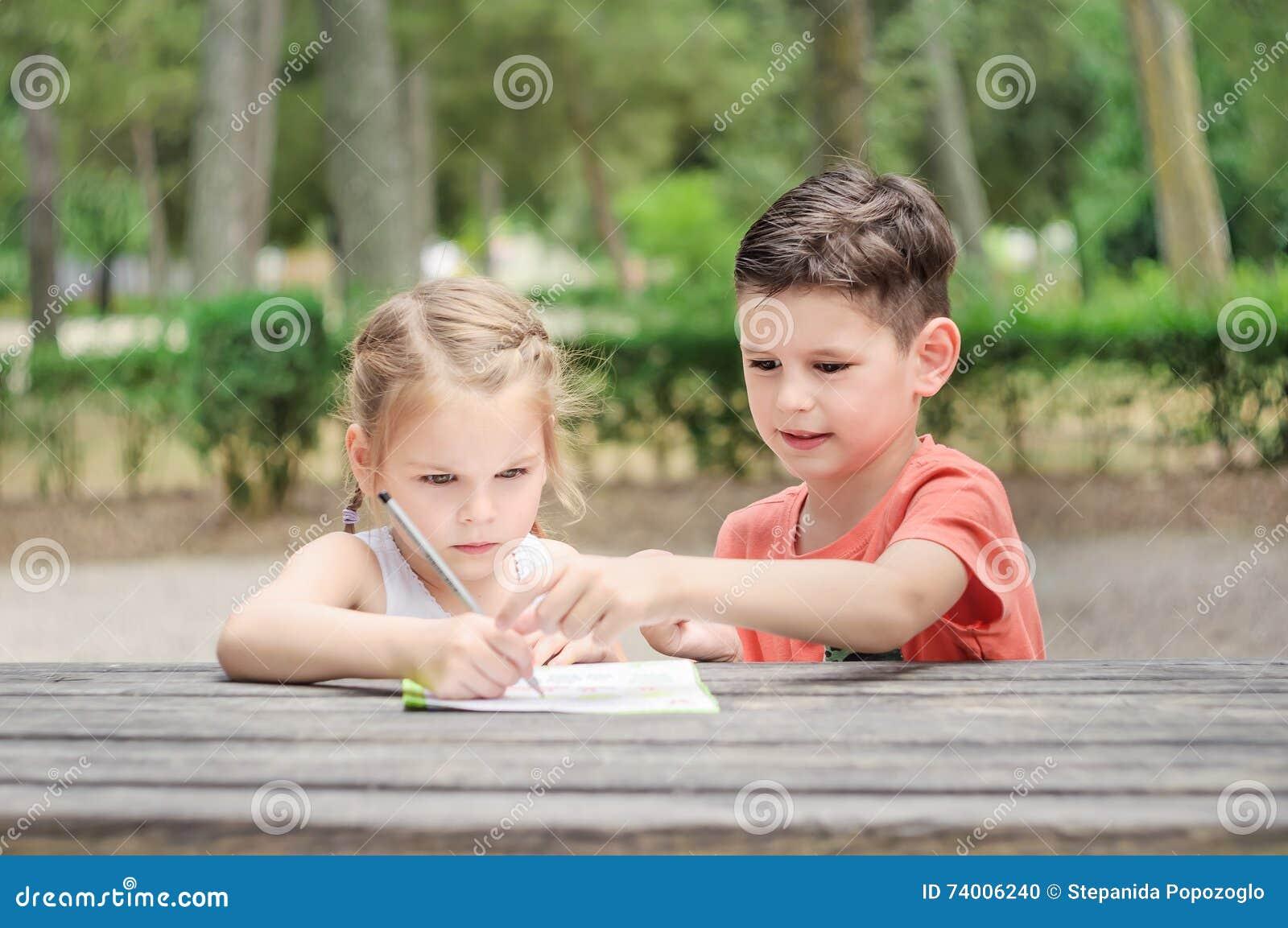 De Hapyjonge geitjes leren in een park De broer en de zuster doen samen j
