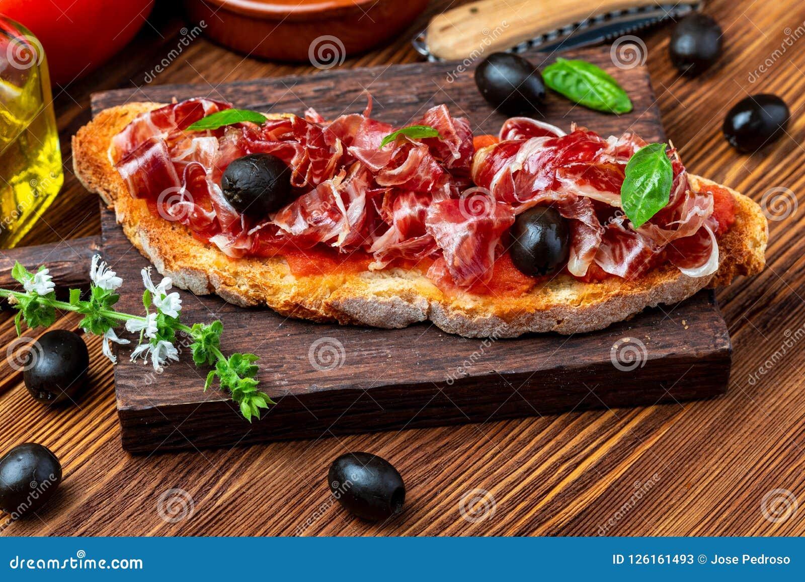 De heerlijke broodtoost met natuurlijke tomaat, extra eerste persing, Iberische ham, zwart olijven en basilicum gaat weg