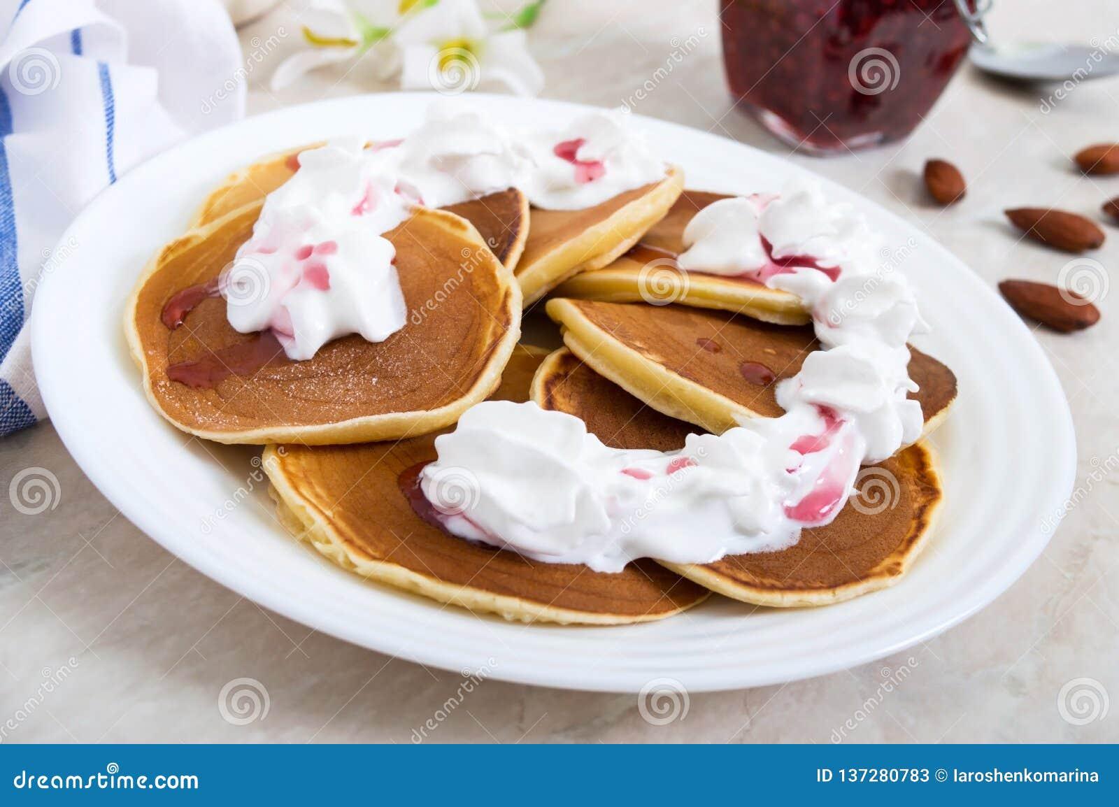 De heerlijke pannekoeken met frambozenjam en slagroom op een wit plateren op de keukenlijst