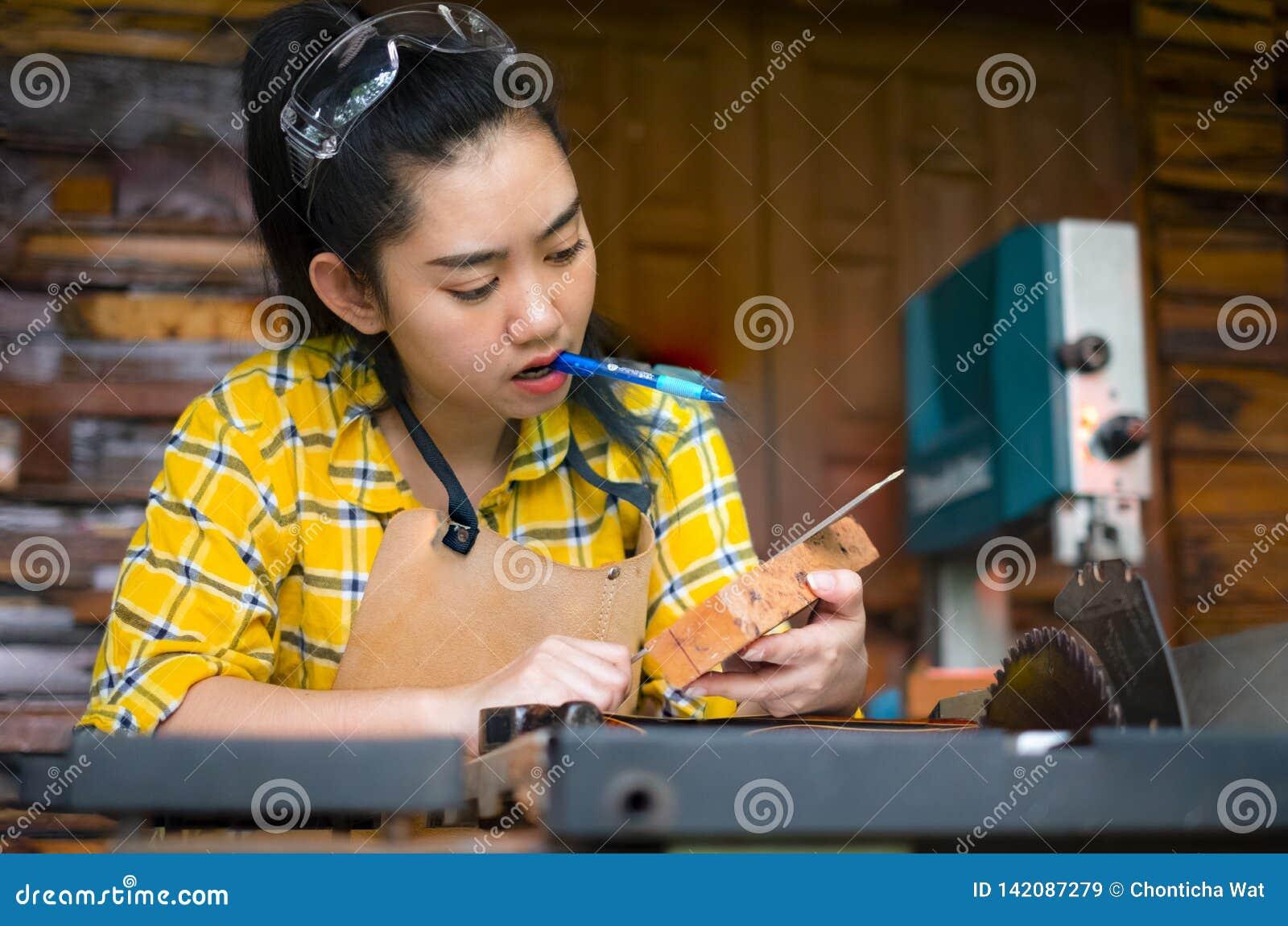 De heerser en het potlood van de vrouwenholding terwijl het maken van tot tekens op het hout de lijst in de workshop