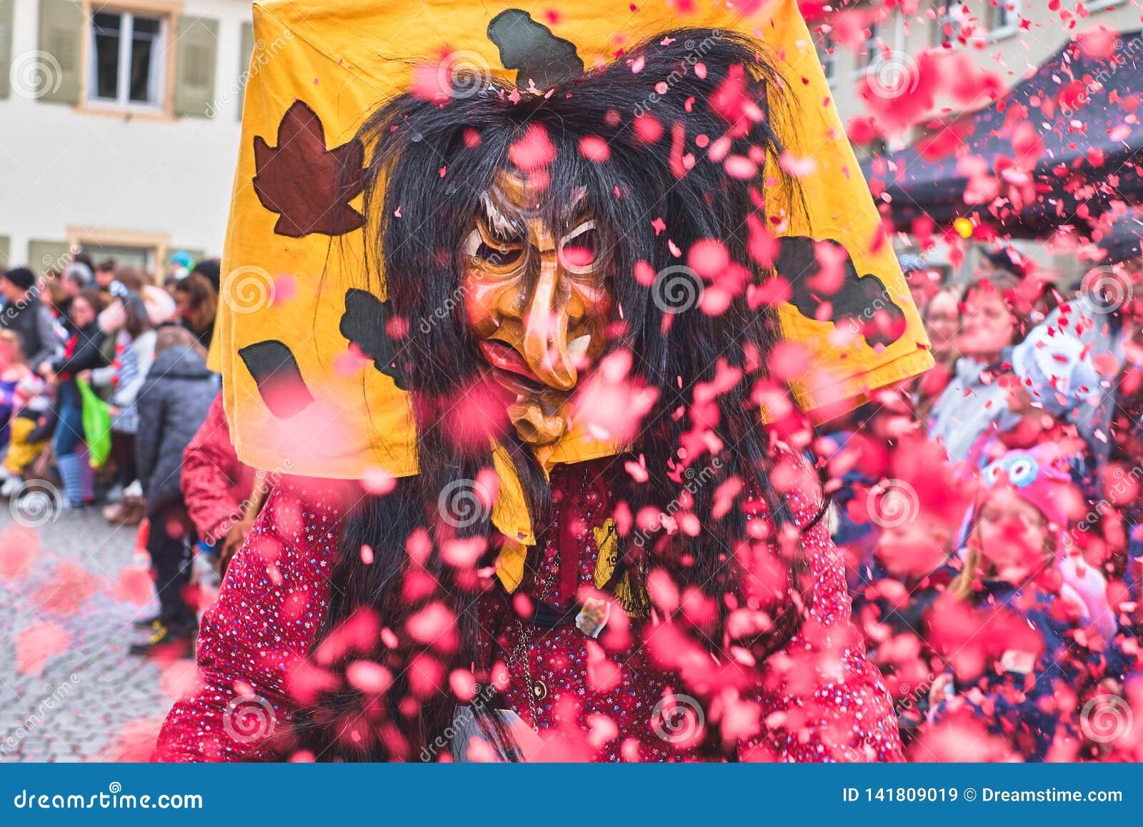 De heks met lang haar werpt rode confettien in de lucht Straat Carnaval in zuidelijk Duitsland - Zwart Bos