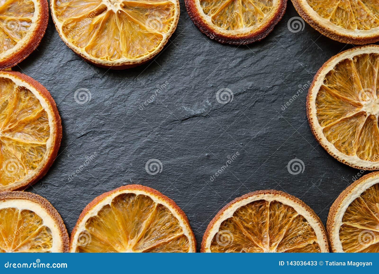 De heldere droge oranje plakken op een steen geweven achtergrond, vlakke exemplaarruimte, leggen, hoogste mening