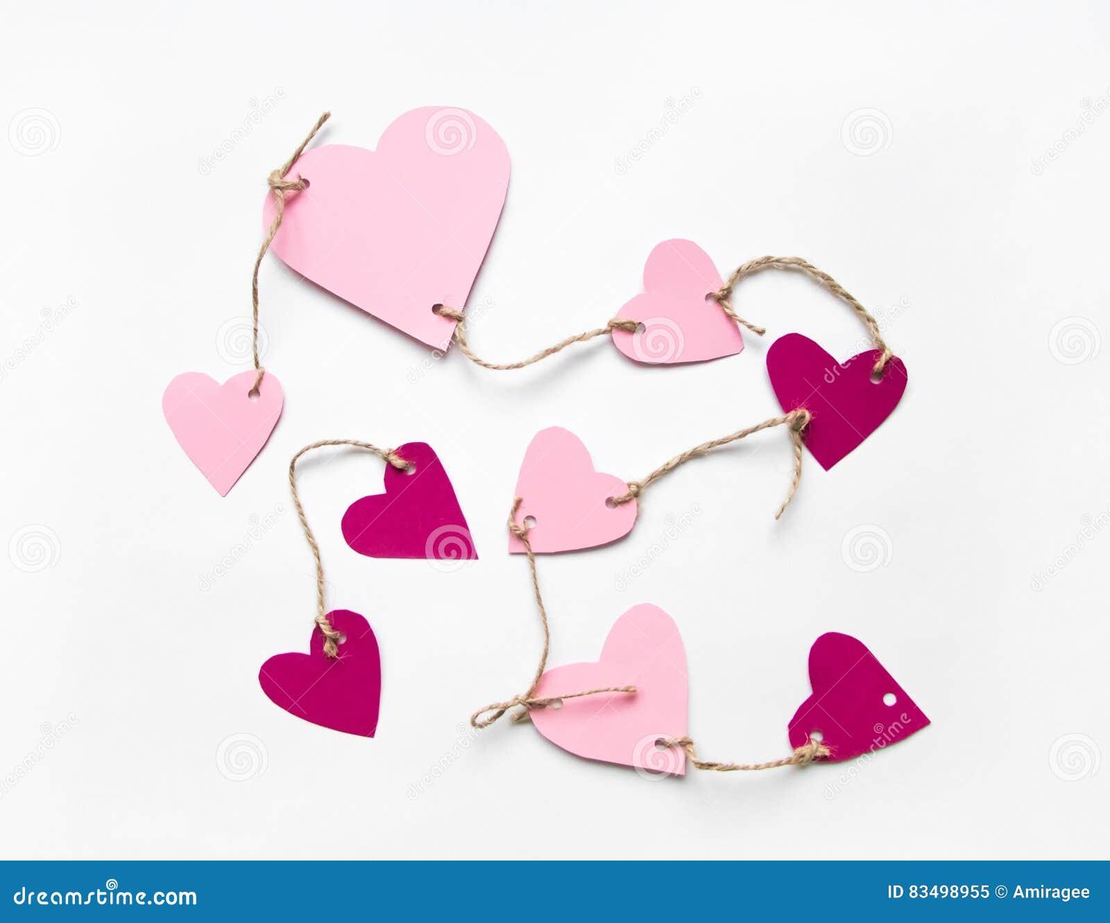 De heldere roze document harten verbonden aan een kabel voor de dag van Valentine ` s Vlak leg op witte achtergrond