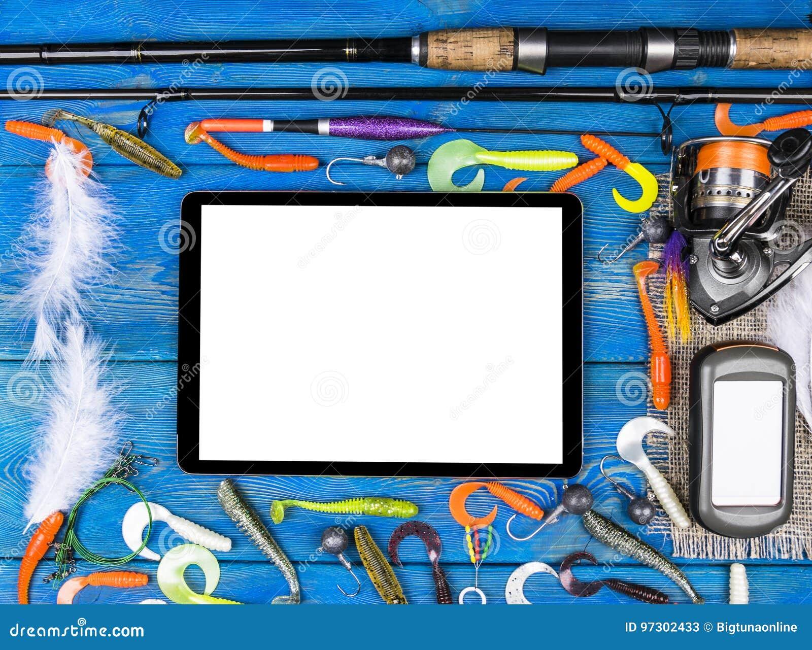 De hengel, de uitrustingen en het vissende aas, spoel op houten raadsachtergrond met tabletcomputer isoleerden het witte scherm,