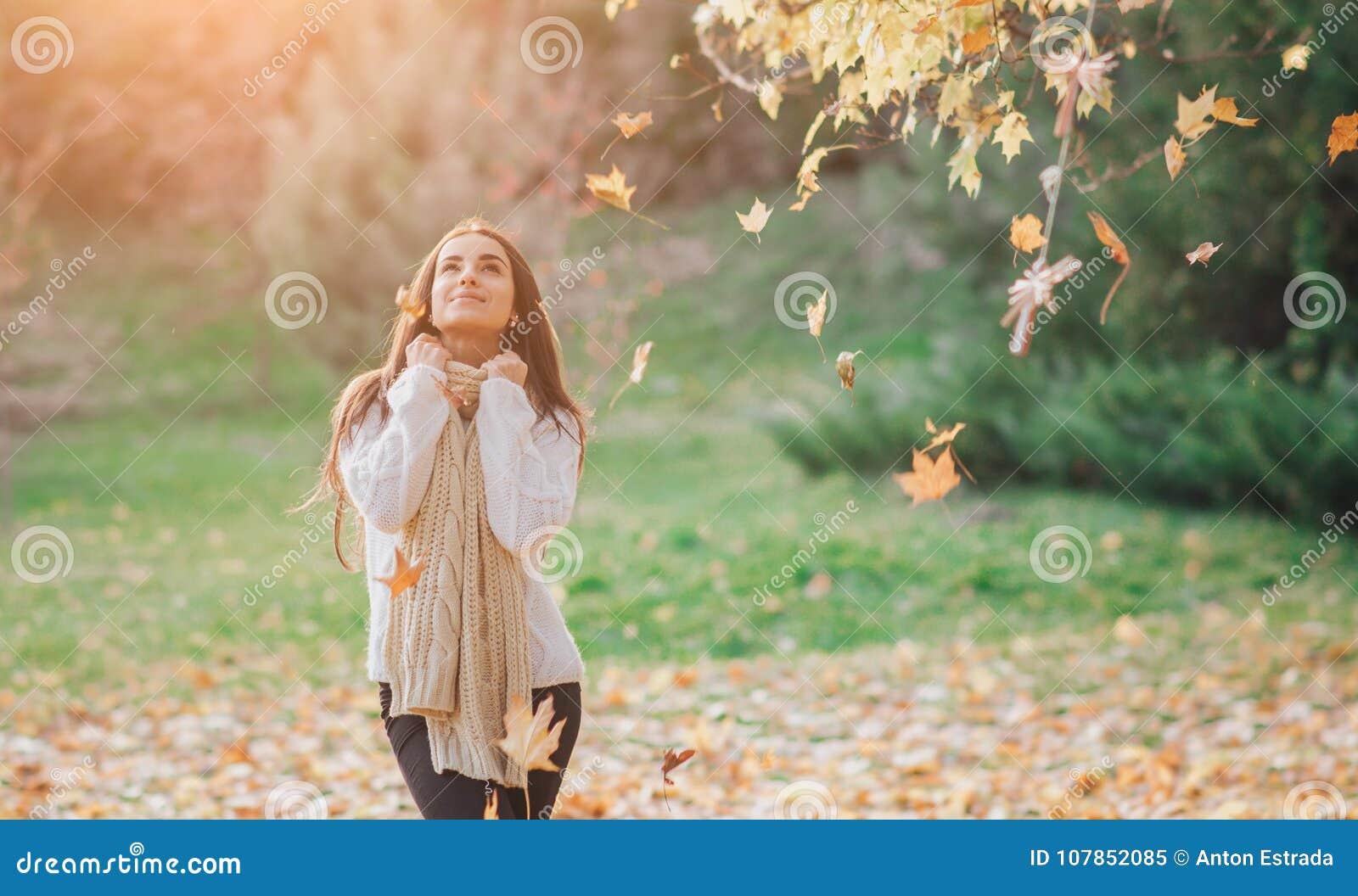 De herfst verlaat het vallen op gelukkige jonge vrouw in bosportret van zeer mooi meisje in dalingspark