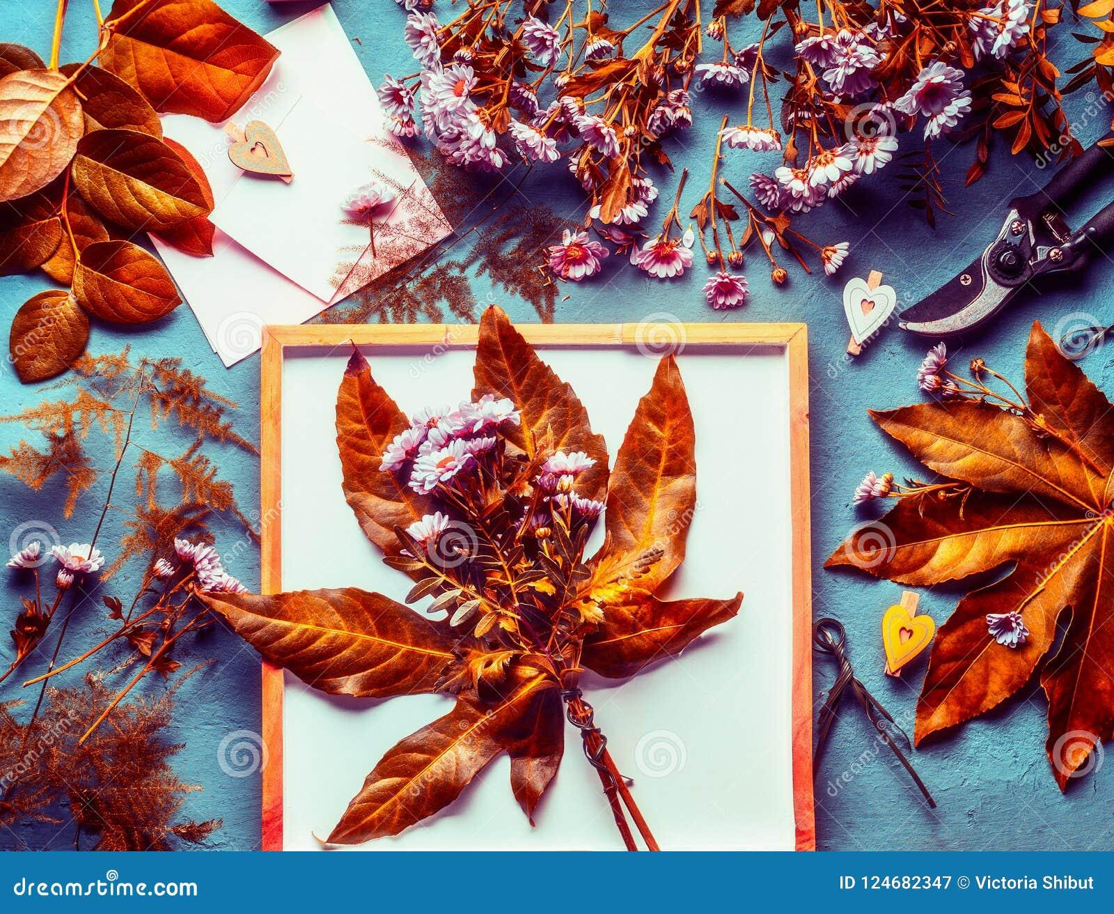 De de herfstbloemen bundelen met oranje bladeren en chrysant op Desktopachtergrond met decoratie en bloemisthulpmiddelen