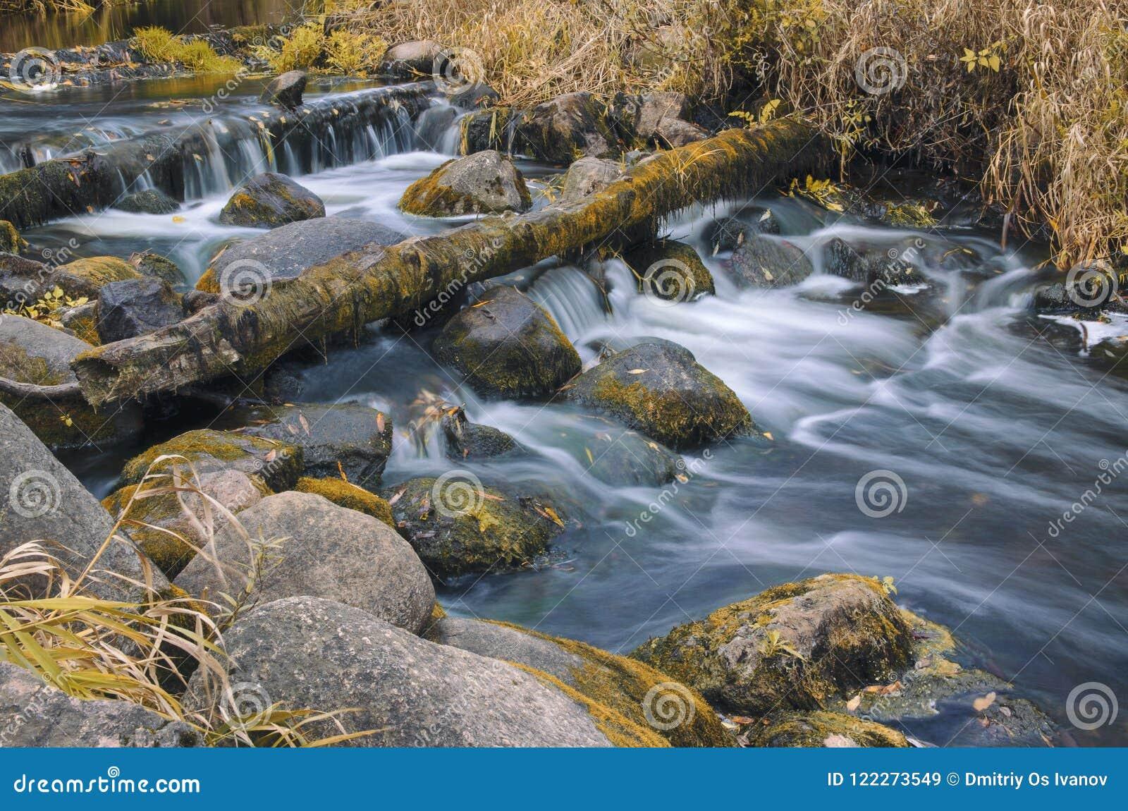 De herfstlandschap met een rivier die regelmatig tussen de keien stromen