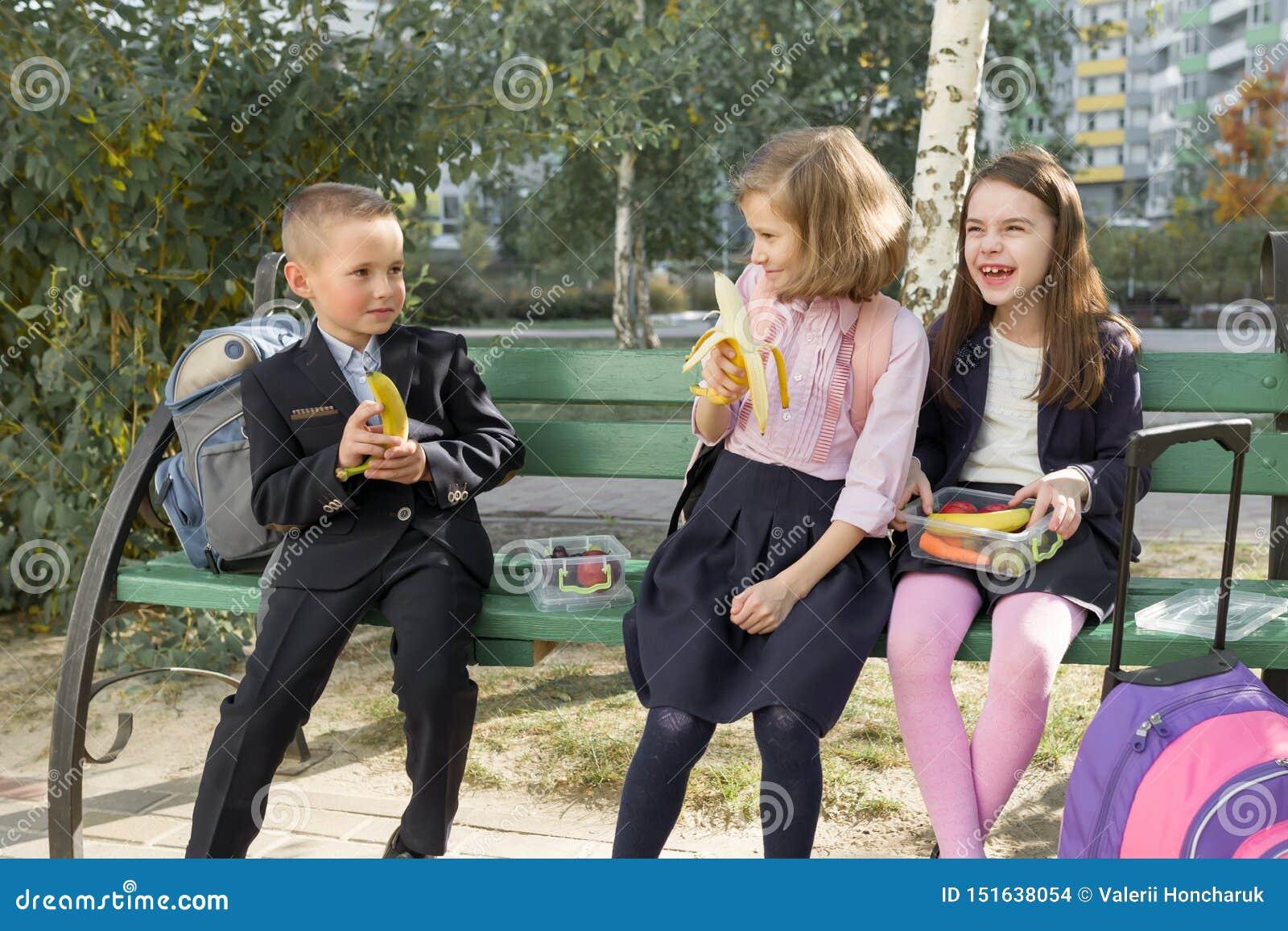 De herfstportret van kinderen met lunchdozen, schoolrugzakken