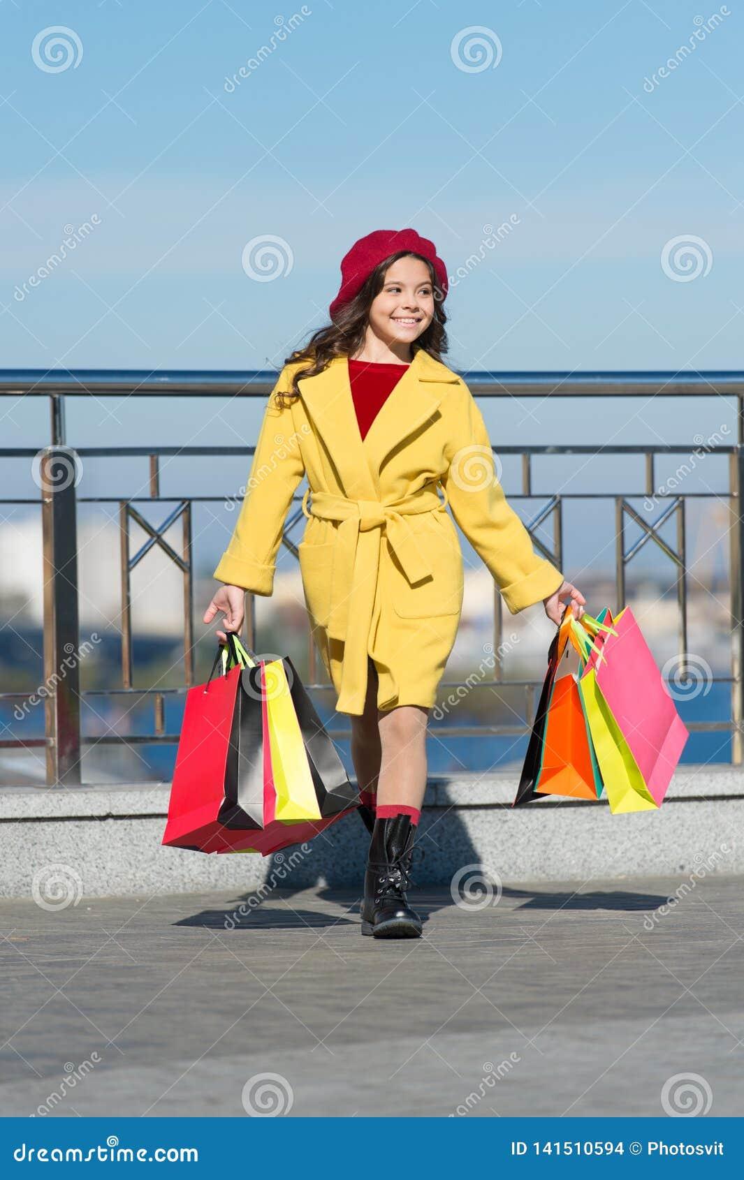 De herfsttendens meisje met aankoop in het winkelen zakken Het winkelen dag Gelukkig meisje De jong geitjemanier ziet eruit styli