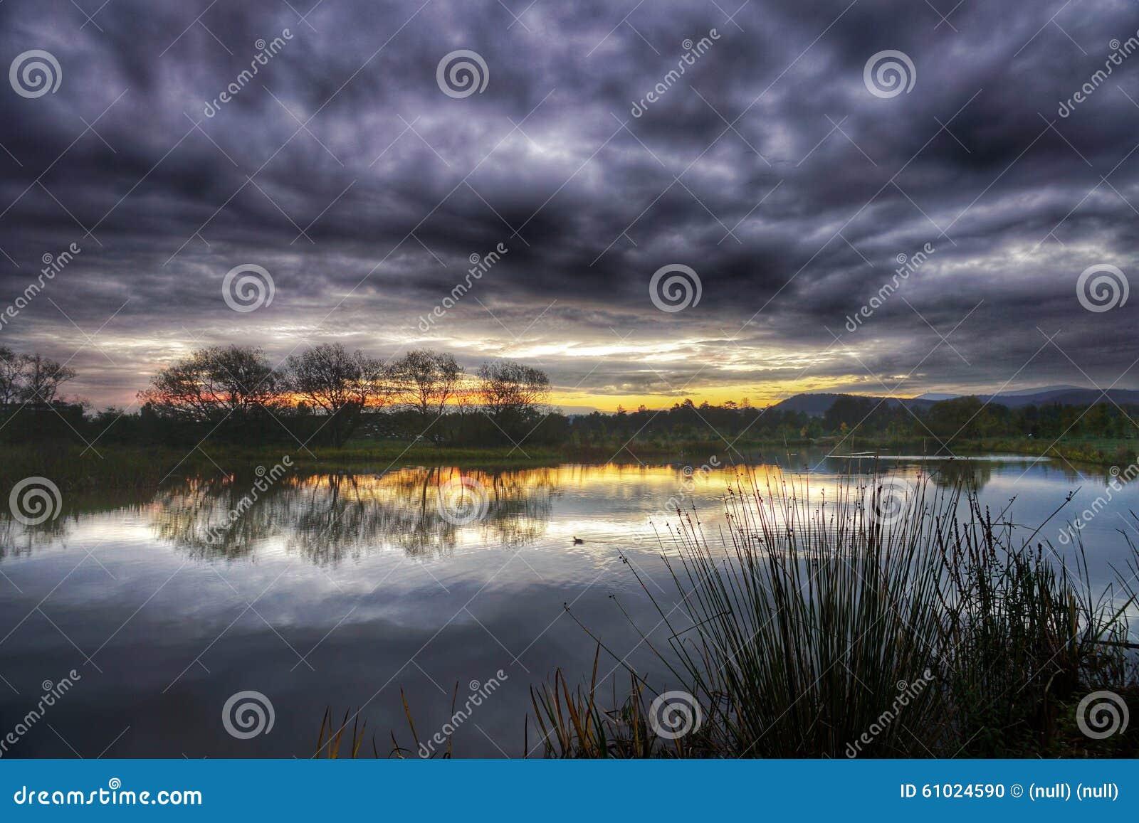 De herfstzonsopgang over een meer