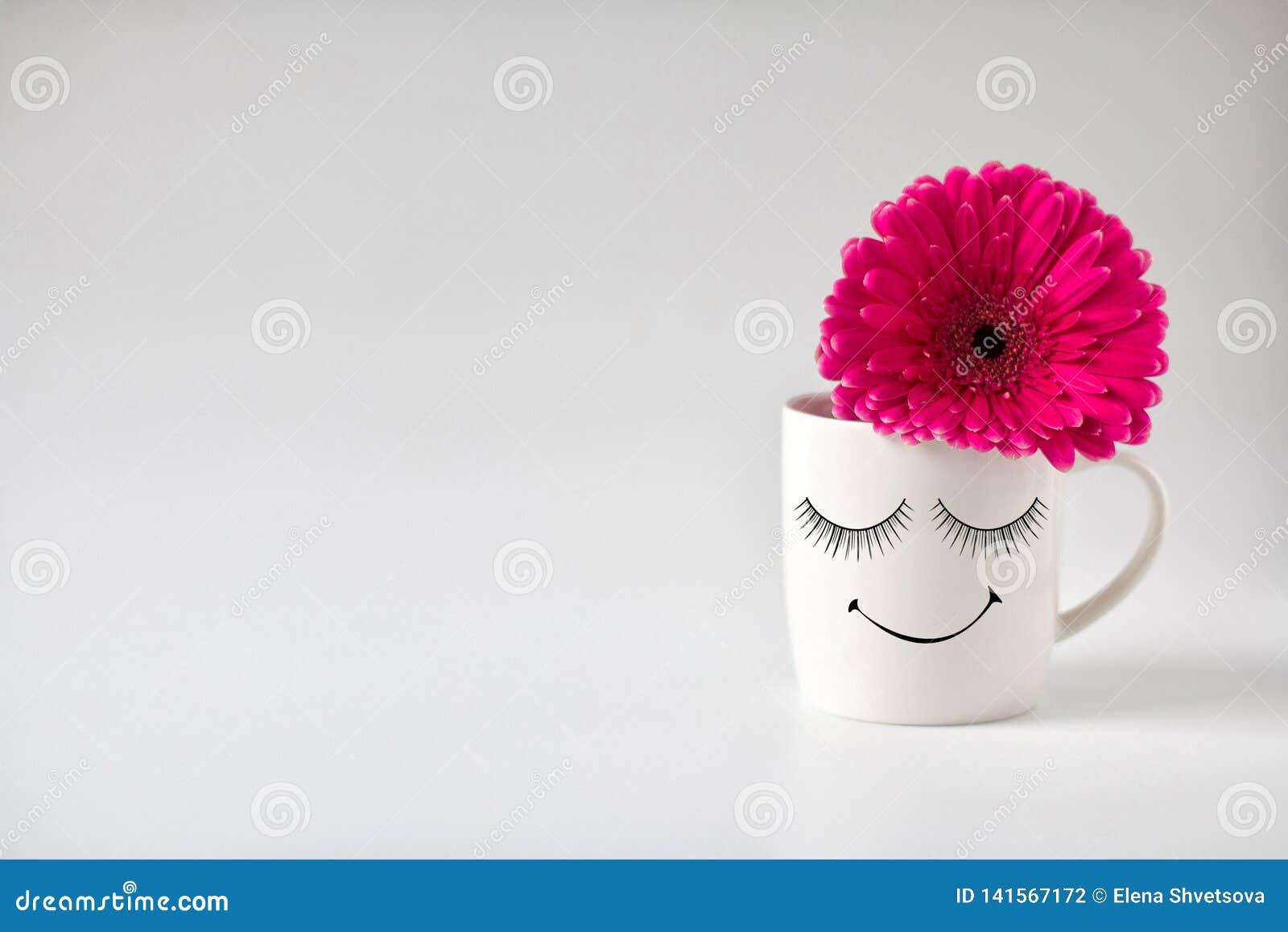 De het glimlachen witte die mok met een bloem van een gerbera op een witte lijst wordt verfraaid