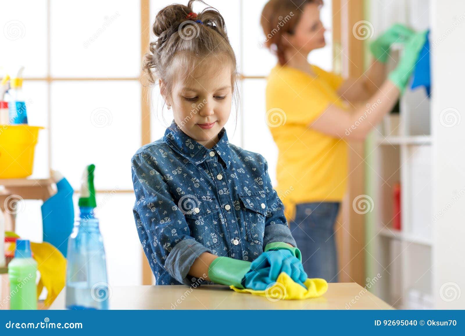 De het jong geitjemeisje en moeder maken thuis het schoonmaken in ruimte