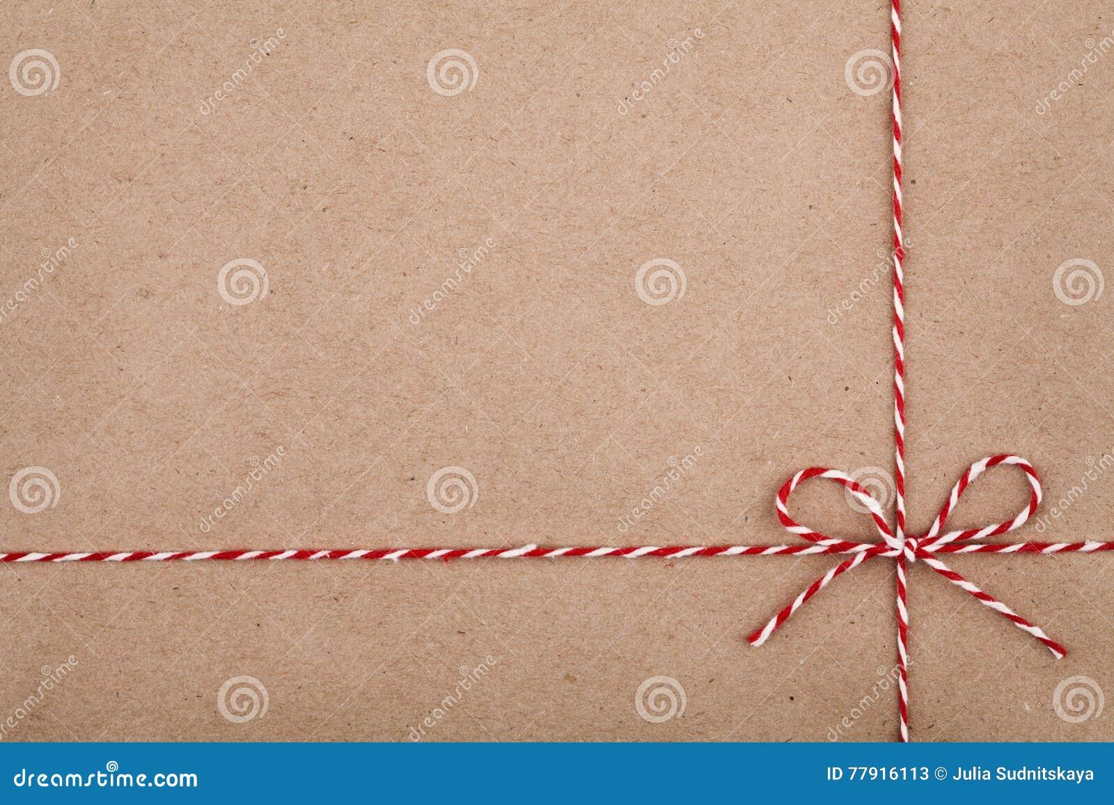 De het Kerstmiskoord of streng bond een boog op kraftpapier-document achtergrond vast