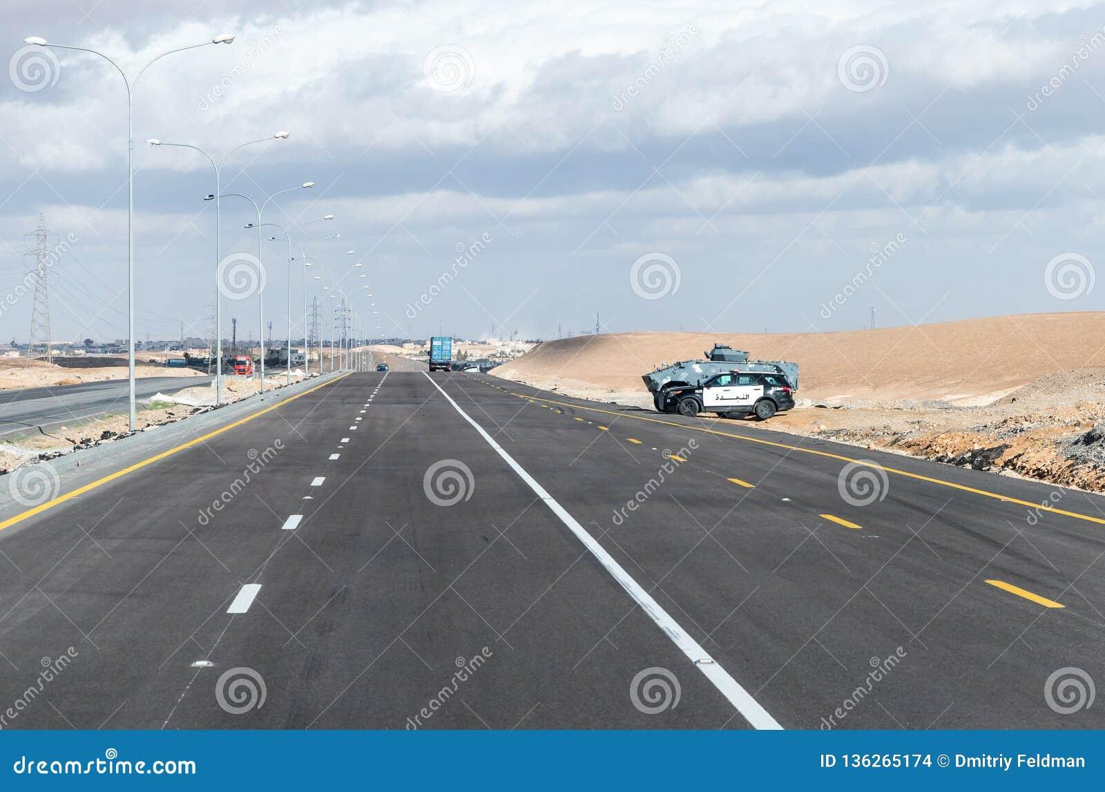 De het verkeerspolitie van Jordanië en de militaire politie bewaken de interlokale route dichtbij Maan-stad in Jordanië