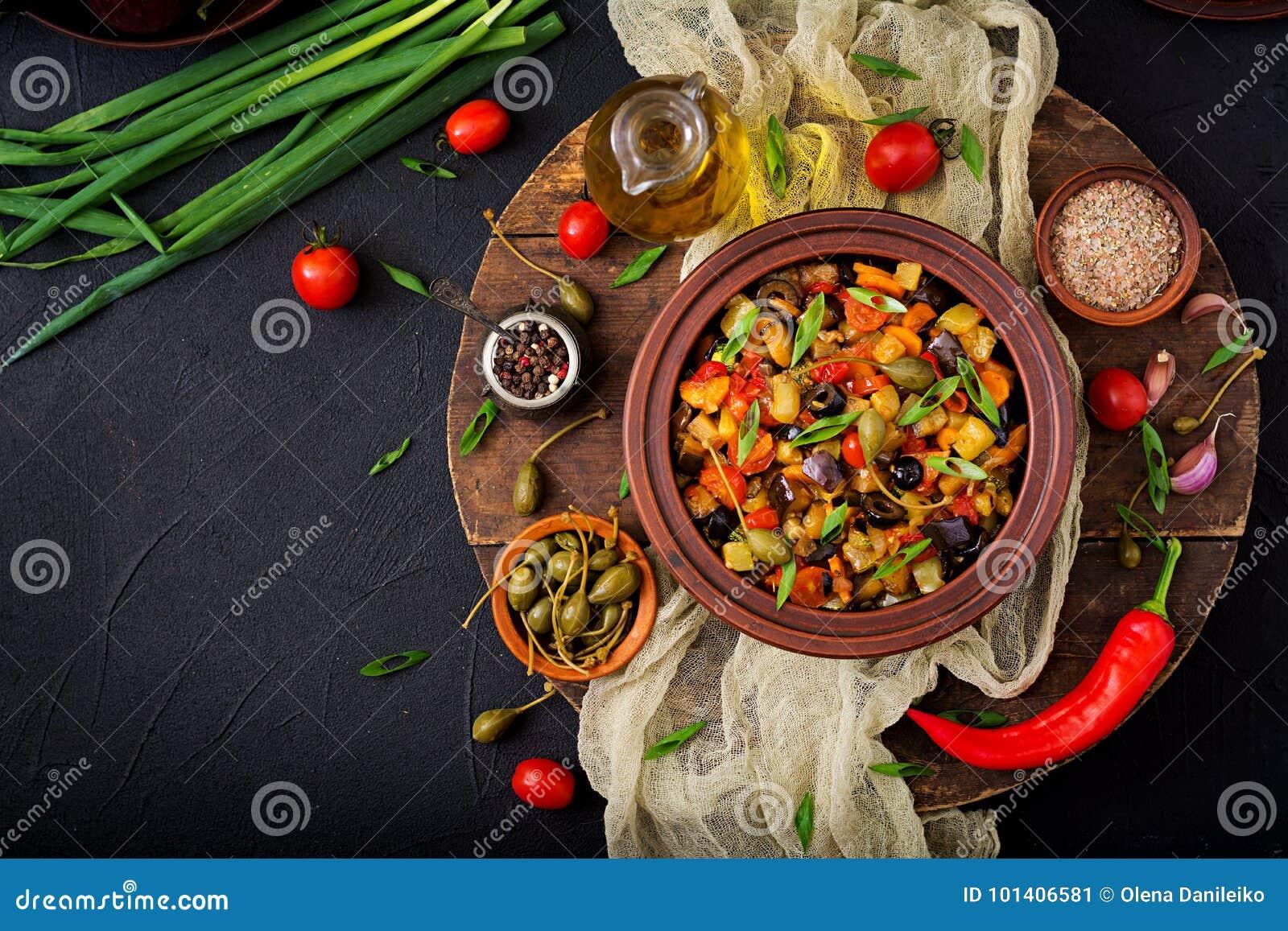 De hete kruidige aubergine van hutspotcaponata, courgette, paprika, tomaat, wortel, ui, olijven en kappertjes