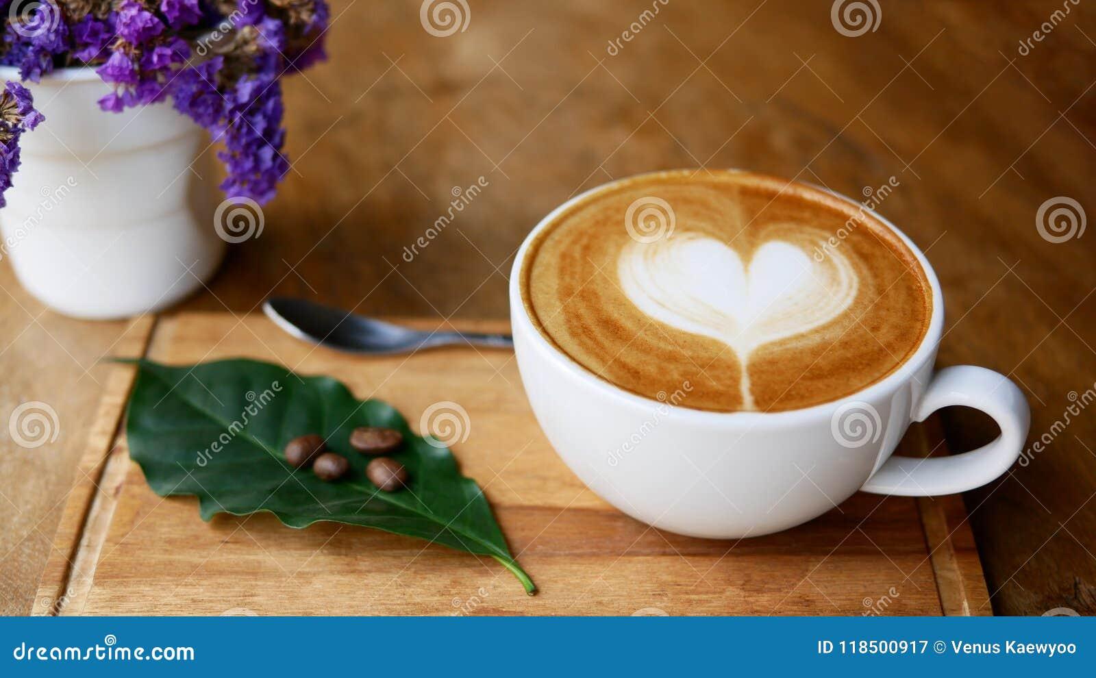 De hete vorm van het de kunsthart van de koffiecappuccino latte in ceramische kop op houten plaat