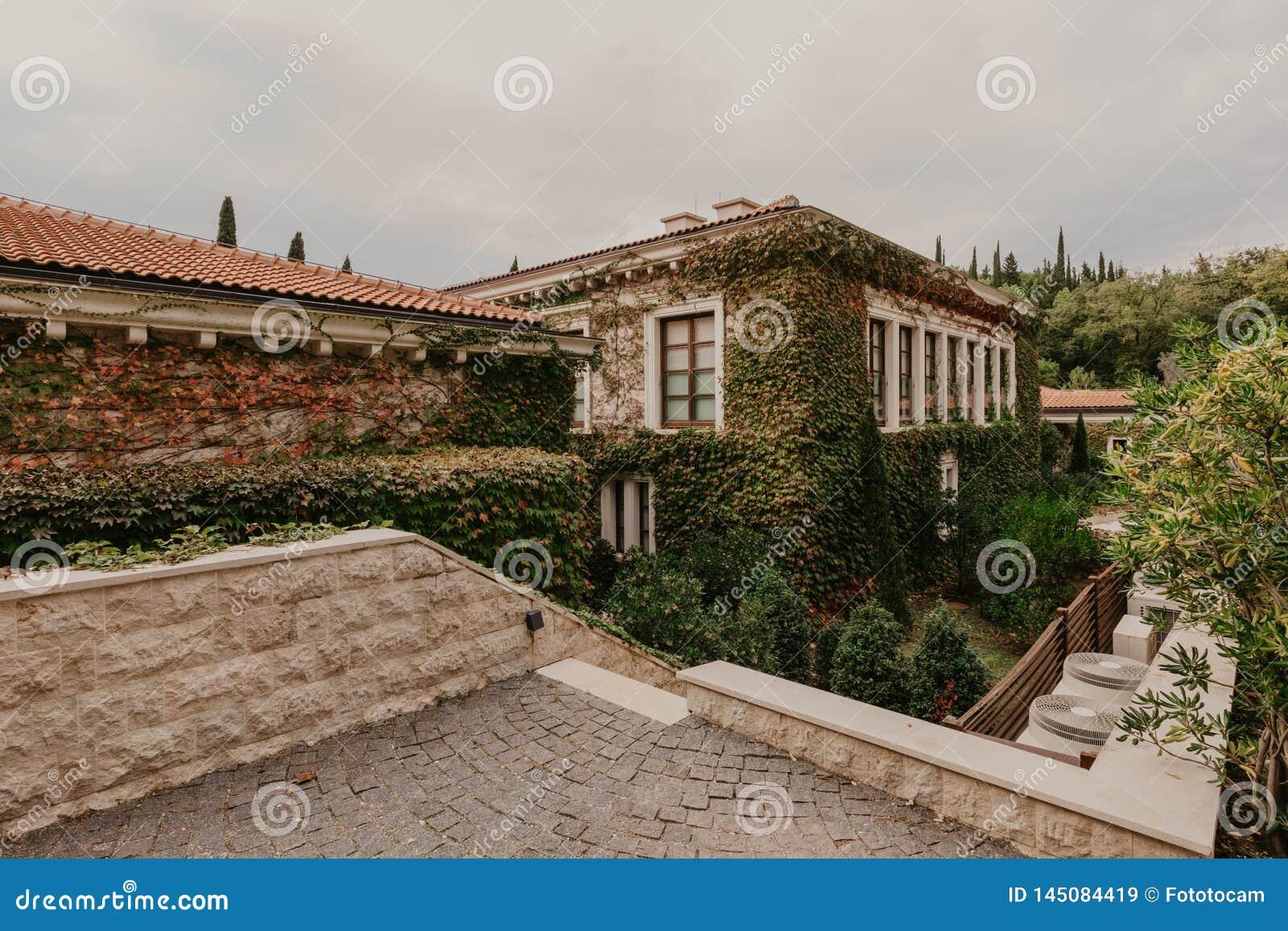 De heuvelige straat met uiterst kleine tuinen, die de plattelandshuisjes en de hotels, Budva Montenegro omringen