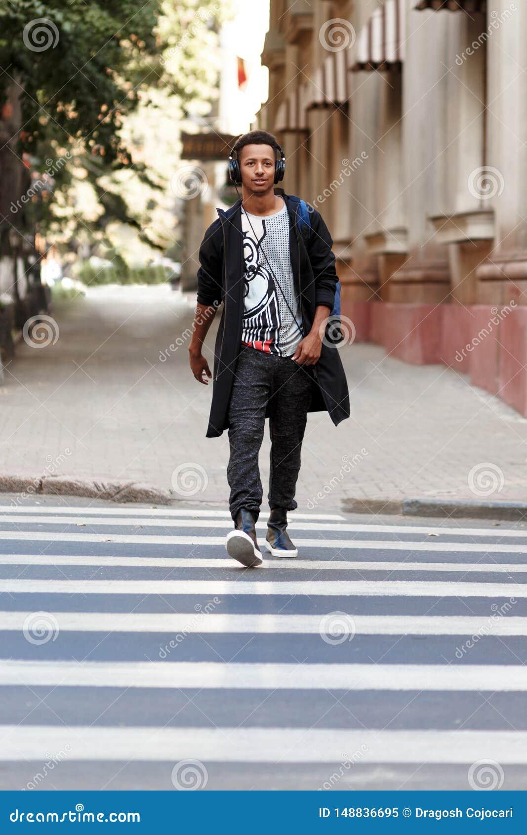 De Hipsterkerel die met atitudine op het zebrapad lopen luisterend een muziek, in dagtijd gaat werken, bevordert het lopen