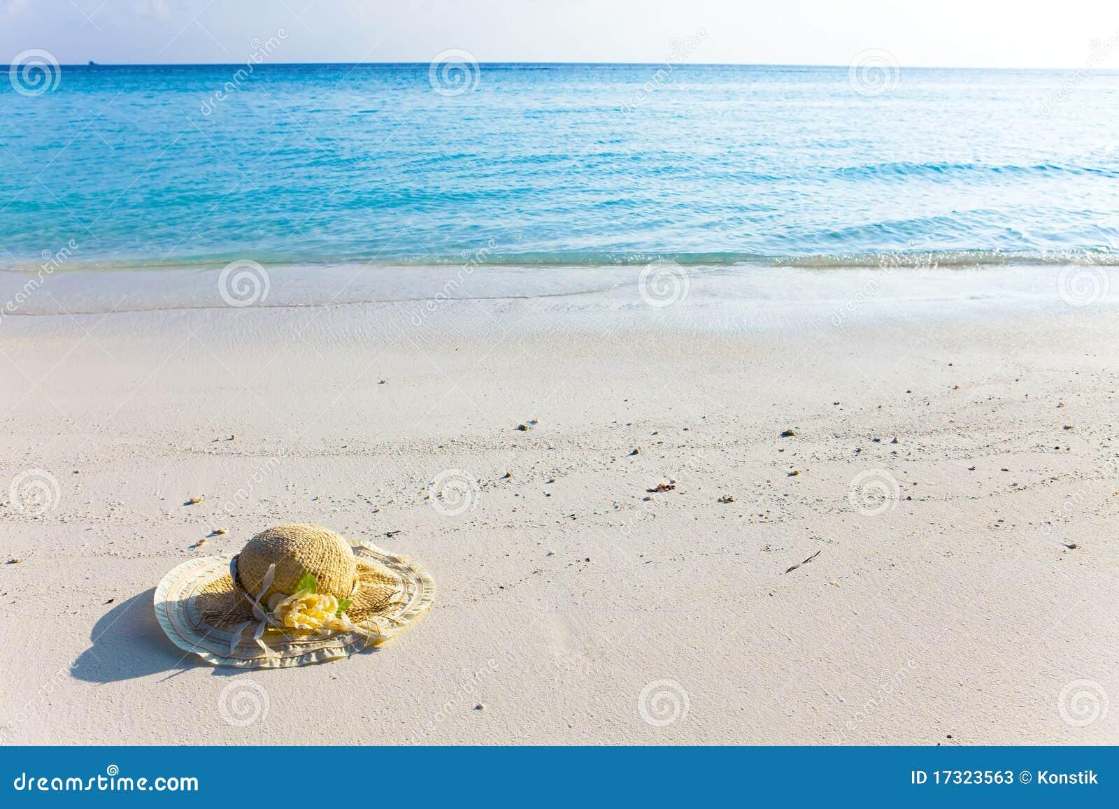 De hoed van het stro legt op zand bij rand van overzees