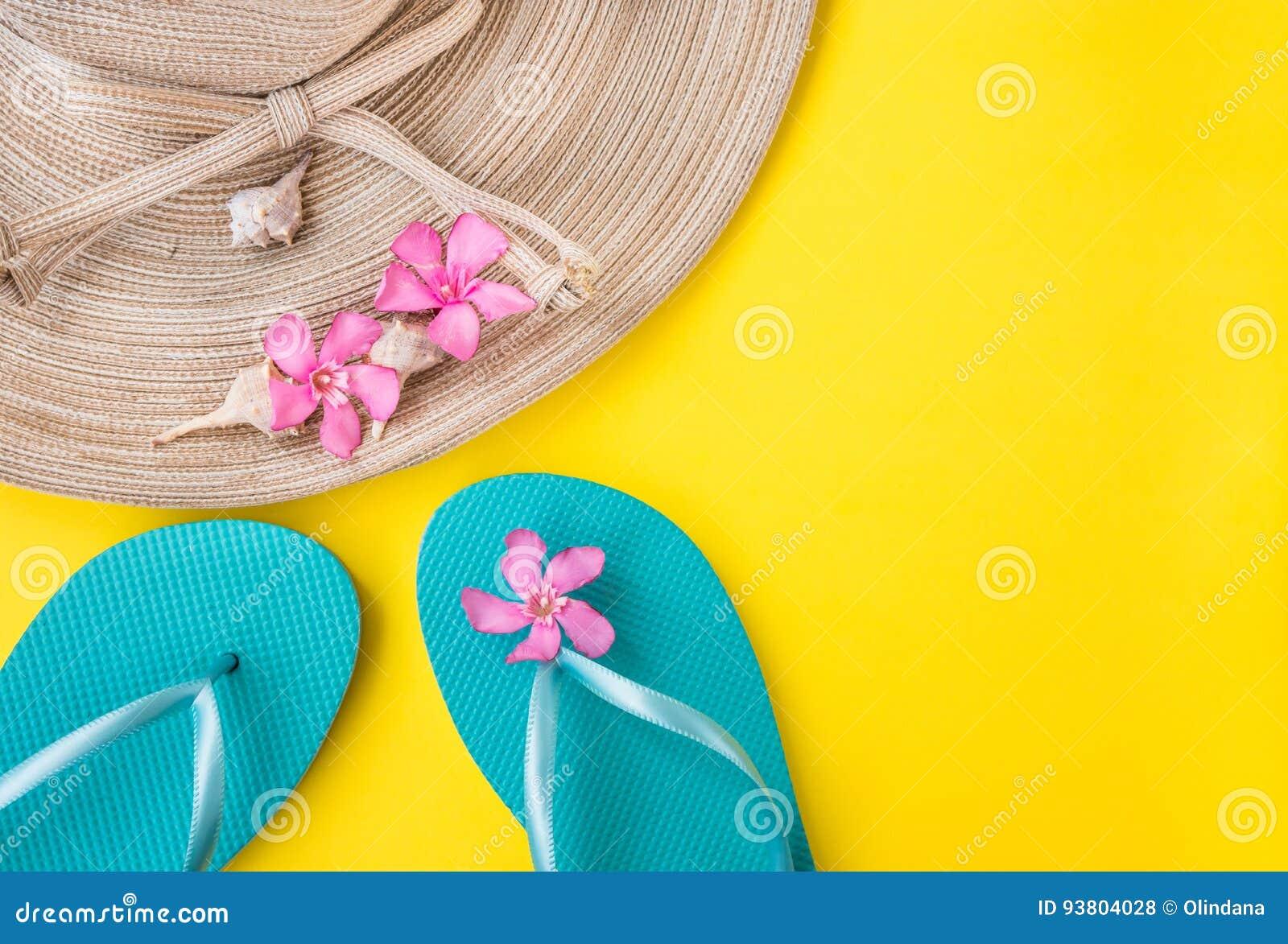 De hoed van het vrouwen` s stro, doorboort tropische bloemen, blauwe pantoffels, overzeese shells, op gele achtergrond, strandvak