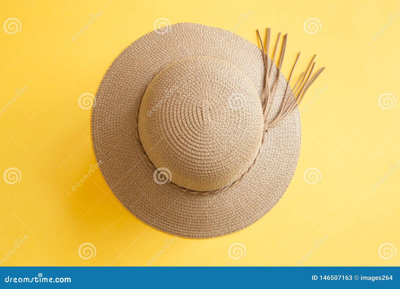 De hoed van de vrouw op gele achtergrond
