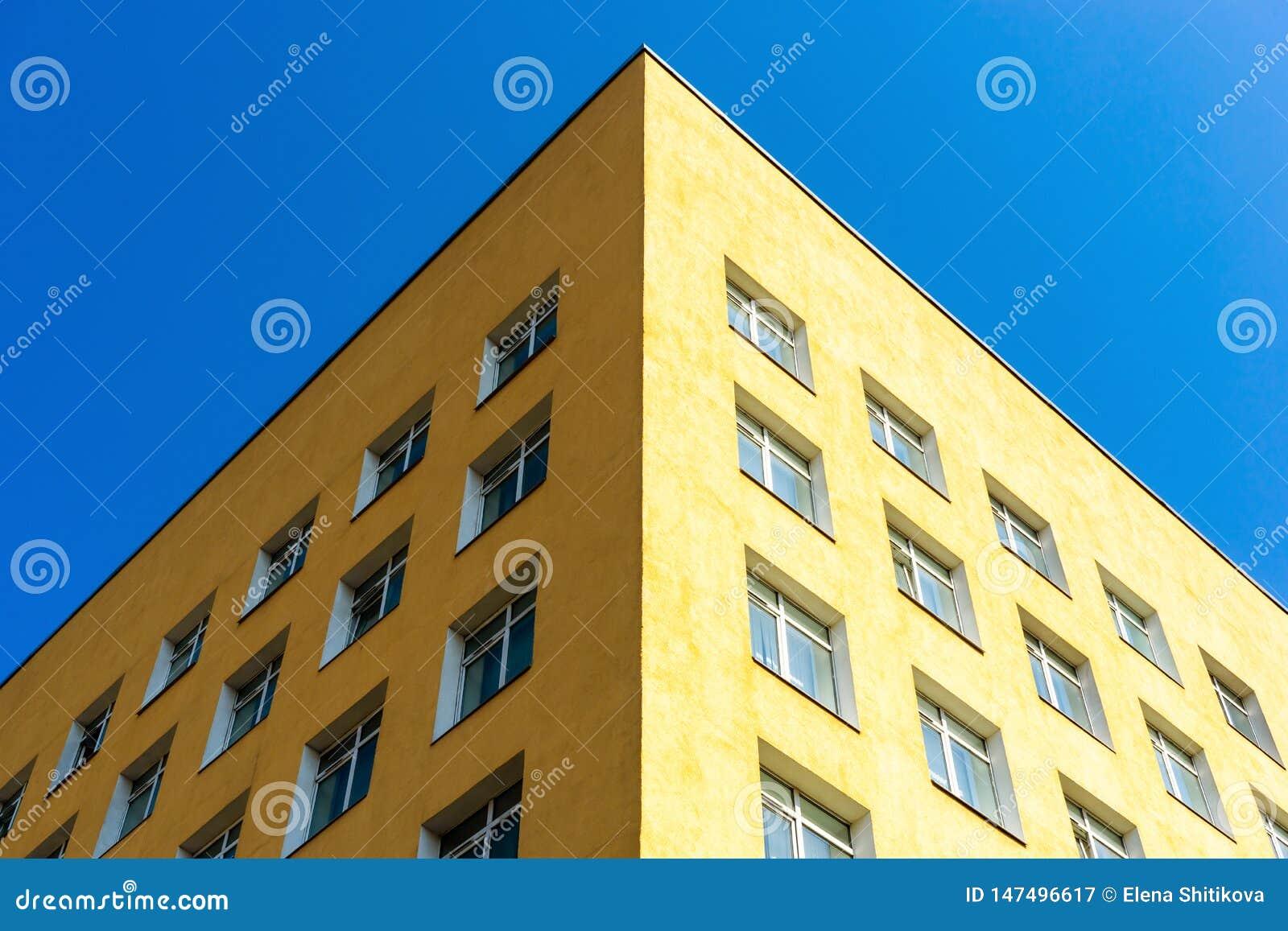De hoek van het gebouw tegen de hemel De architectuur van de stad