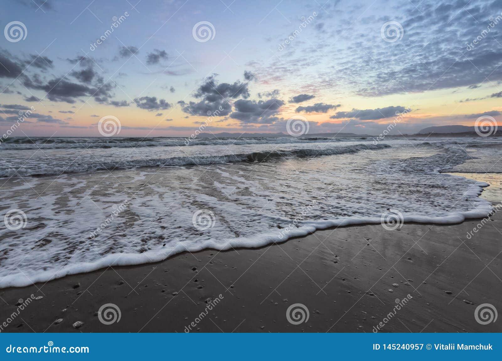 De hoge golven met schuim spreiden op het zand op de kust uit het licht van ongelooflijke zonsondergang het overzees overdenkt Be