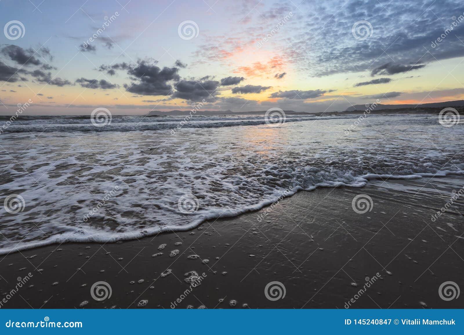 De hoge golven met schuim spreiden op het zand op de tijd van de kust Predageraad uit Het licht van ongelooflijke zonsondergang o