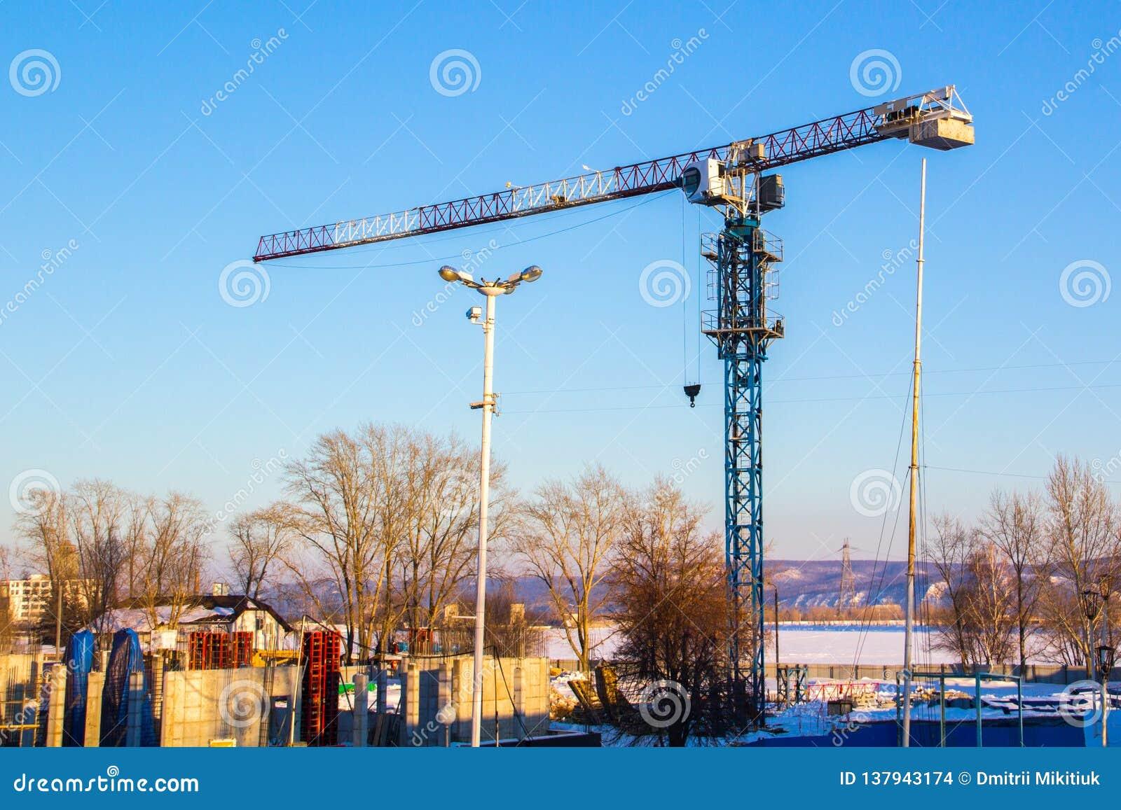 De hoge kraan van de liftbouw met witte, rode en blauwe kleuren tegen een blauwe hemel