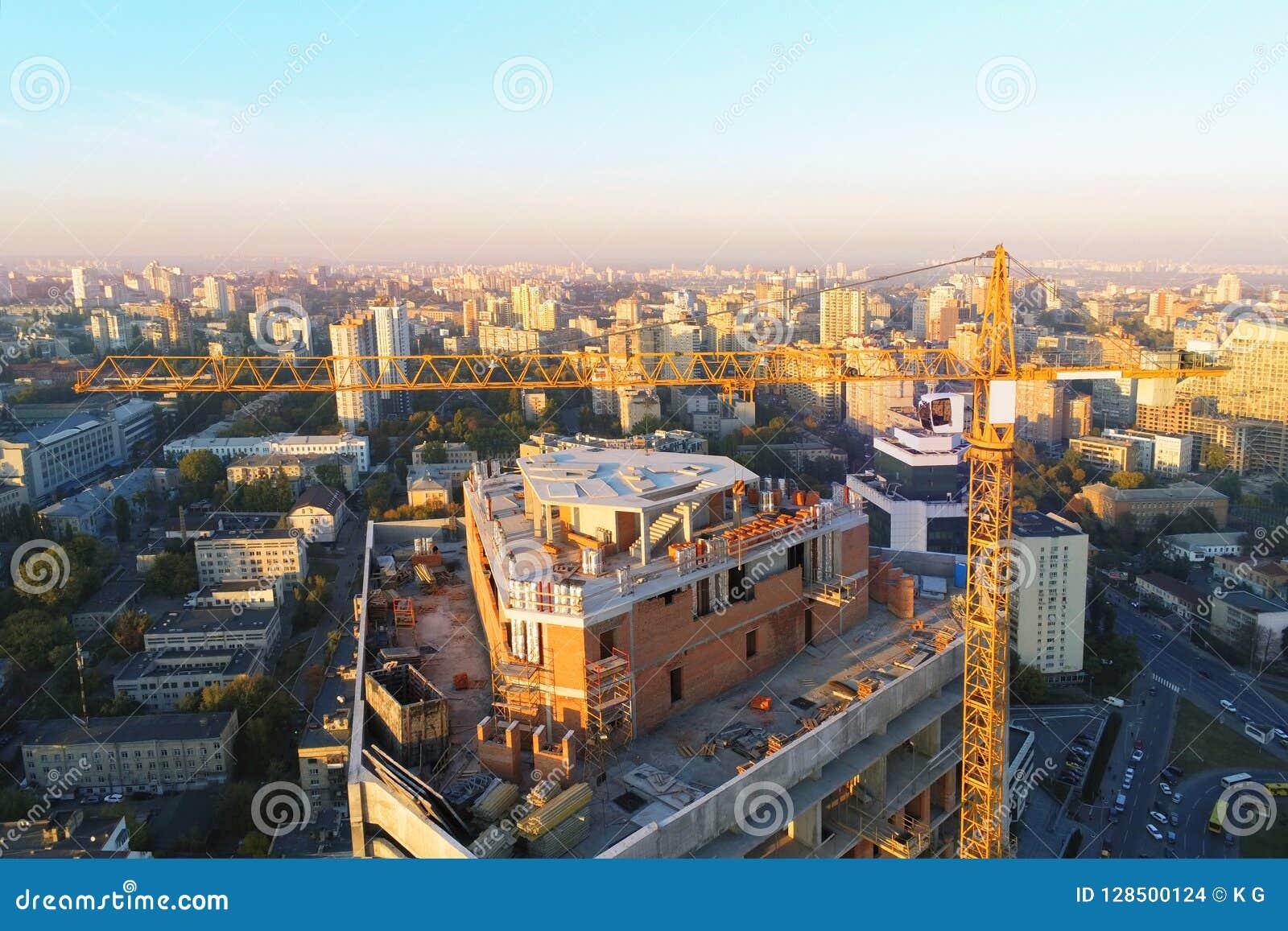 De hoge plaats van de torenbouwconstructie Insecten industriële kraan Luchthommelmening De stadsontwikkeling van de metropool