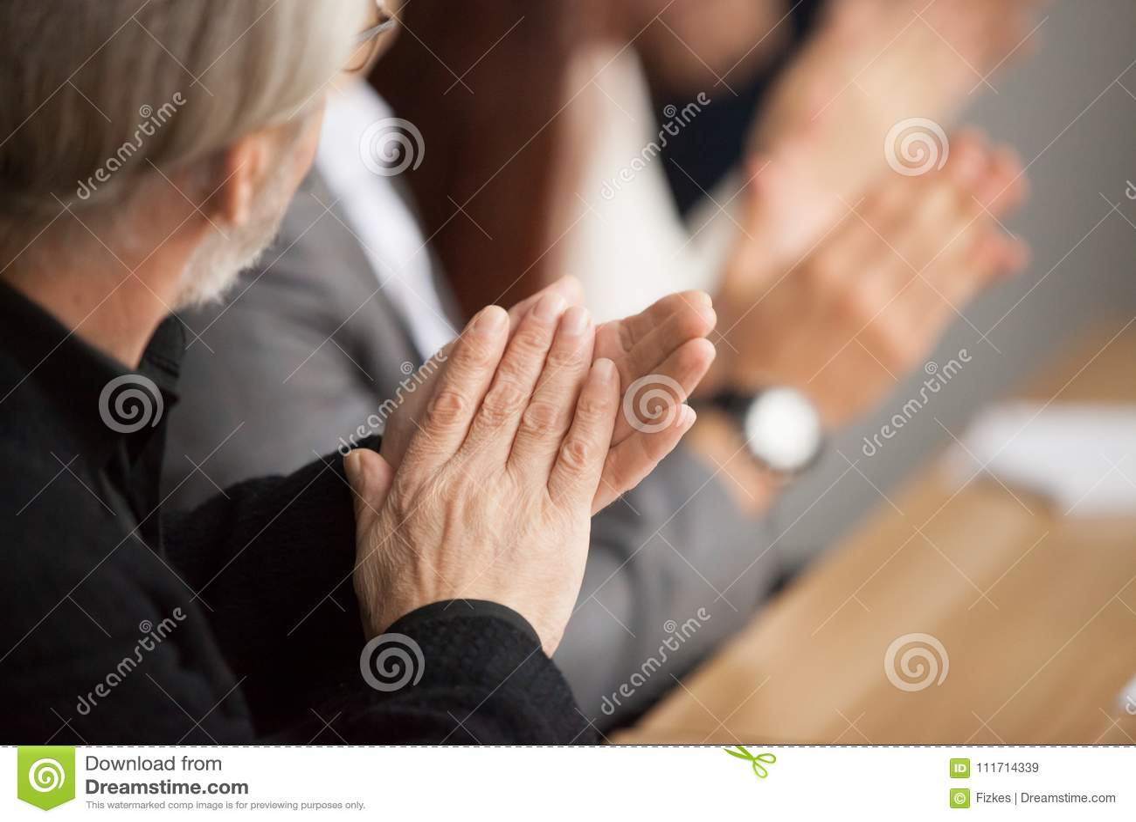 De hogere grijs-haired zakenman die handen het aanwezig zijn slaan conferen
