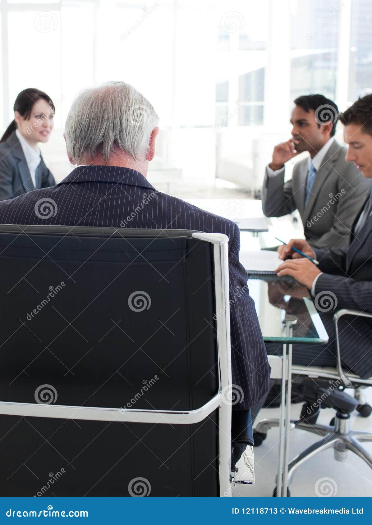 De hogere manager bekeek van erachter in een vergadering