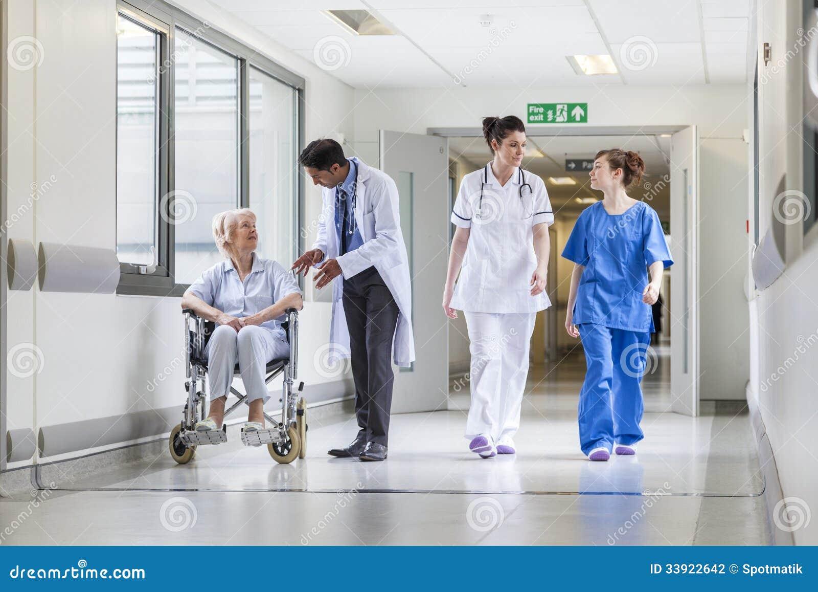De hogere Vrouwelijke Patiënt van de artsenverpleegster in het Ziekenhuisgang