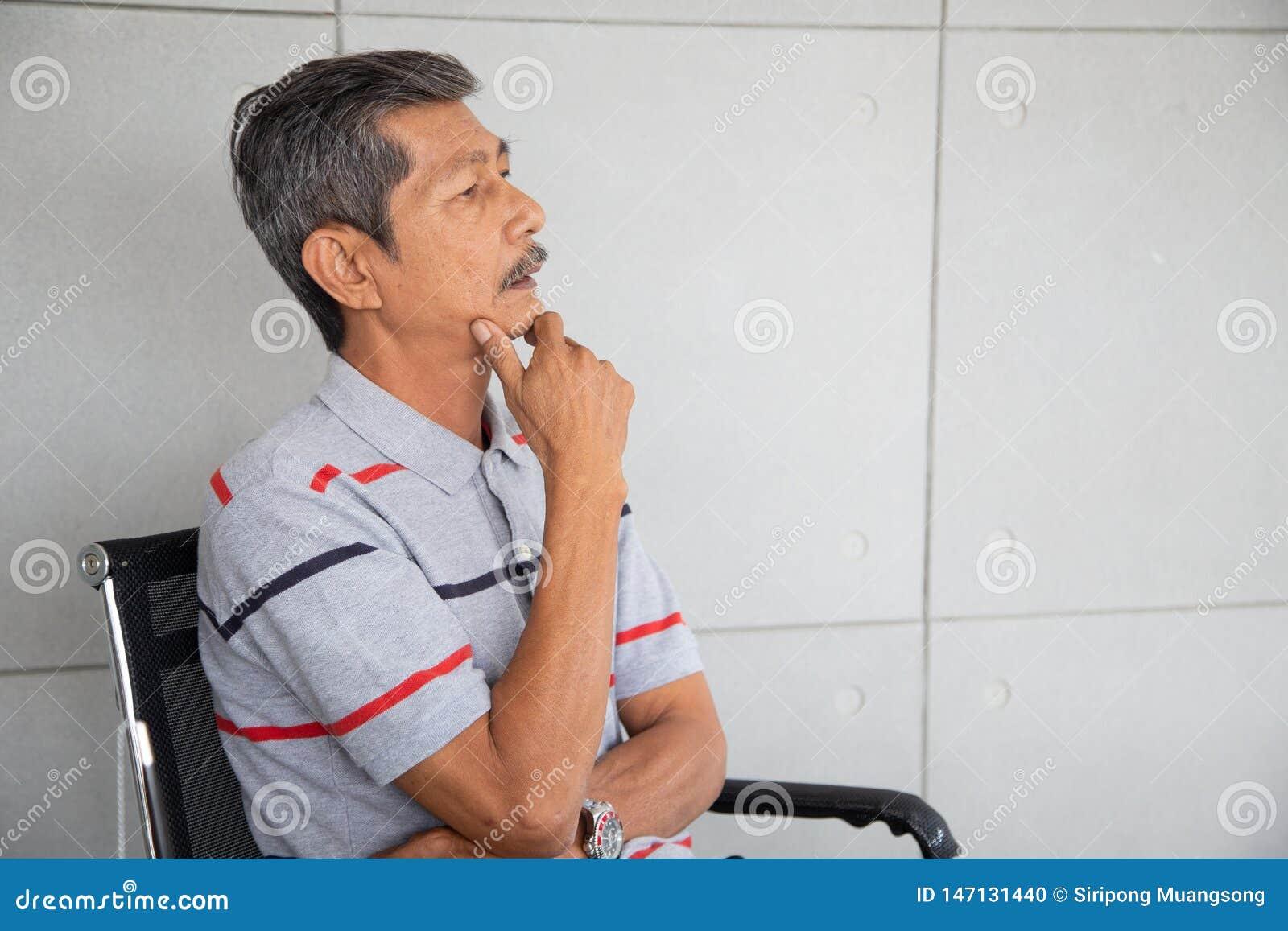 De hogere zakenman van Azië zit en denkend