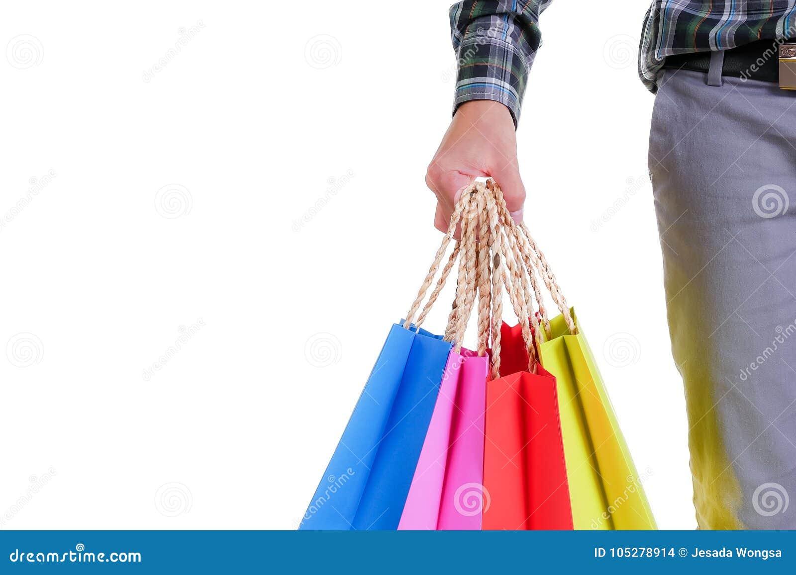 De holding van de mensenhand het winkelen zakken op witte achtergrond worden geïsoleerd die