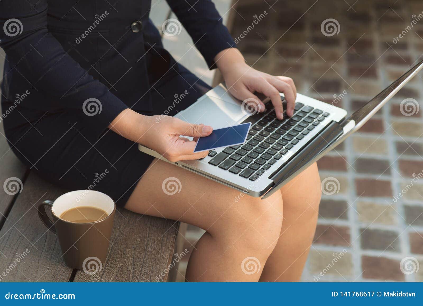 De holdingscreditcard van de vrouwenhand en laptop dichte omhooggaande buitenkant