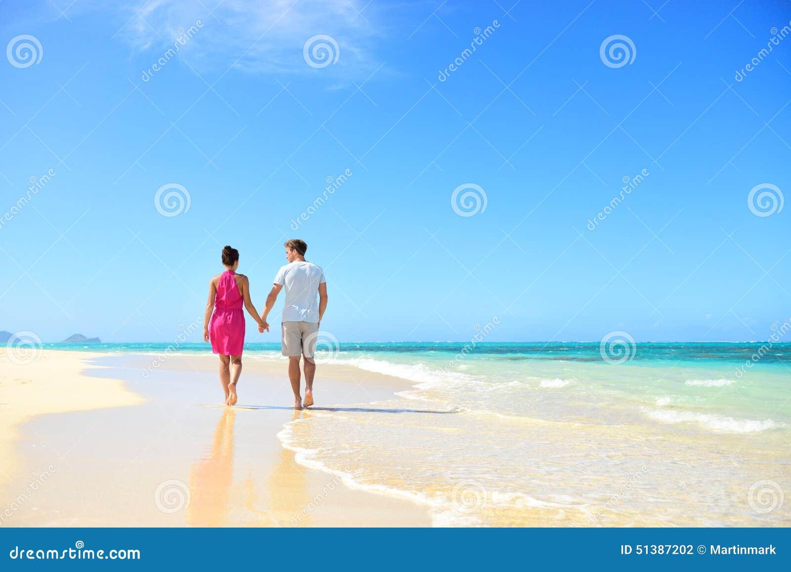 De holdingshanden die van het strandpaar op wittebroodsweken lopen
