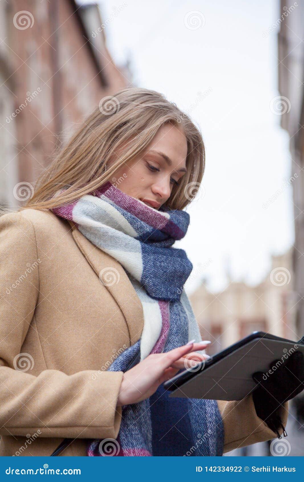 De holdingstablet van de blonde mooie vrouw op stadsstraat