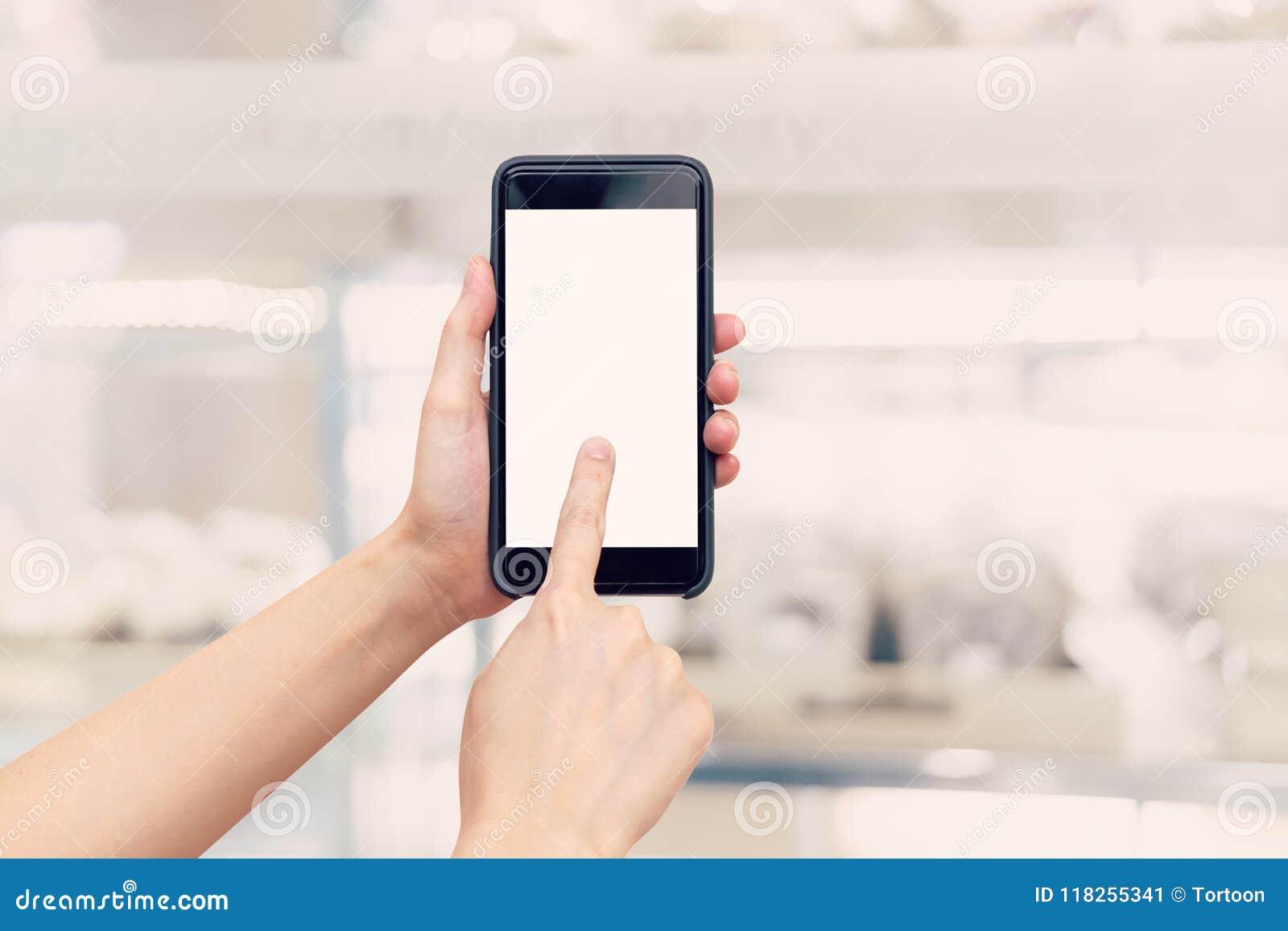 De holdingstelefoon van de handvrouw met het lege het scherm en onduidelijk beeld winkelen mal