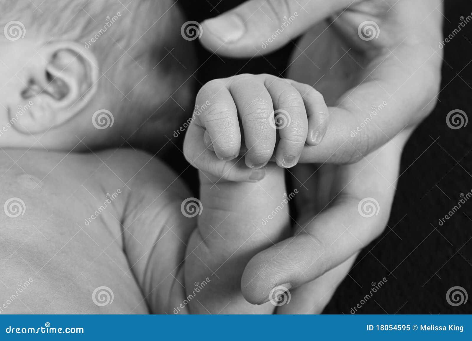 De holdingsvinger van de baby van ouder
